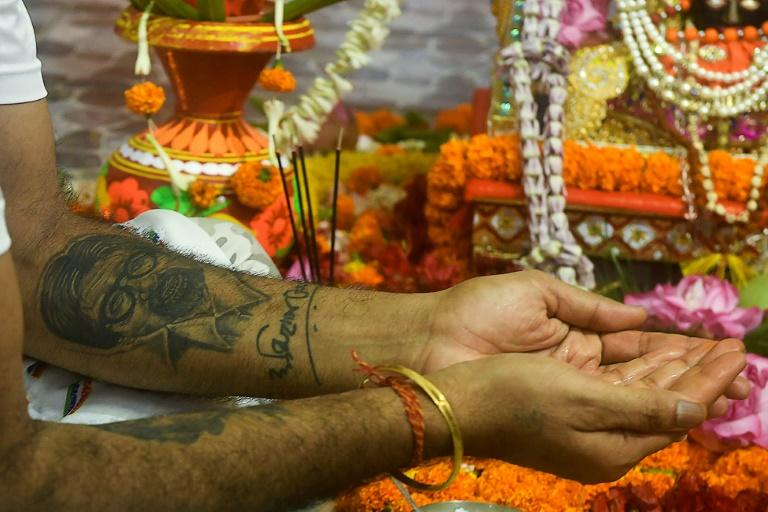 A fan with a tattoo of Amitabh Bachchan on his arm takes part in a ceremony praying for the Bollywood star's recovery from coronavirus in Kolkata (AFP Photo/Dibyangshu SARKAR)