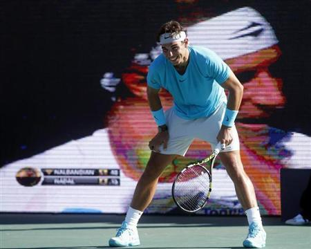 Spain's Nadal smiles as Argentina's Nalbandian is seen on a large television screen during their exhibition tennis match in Buenos Aires