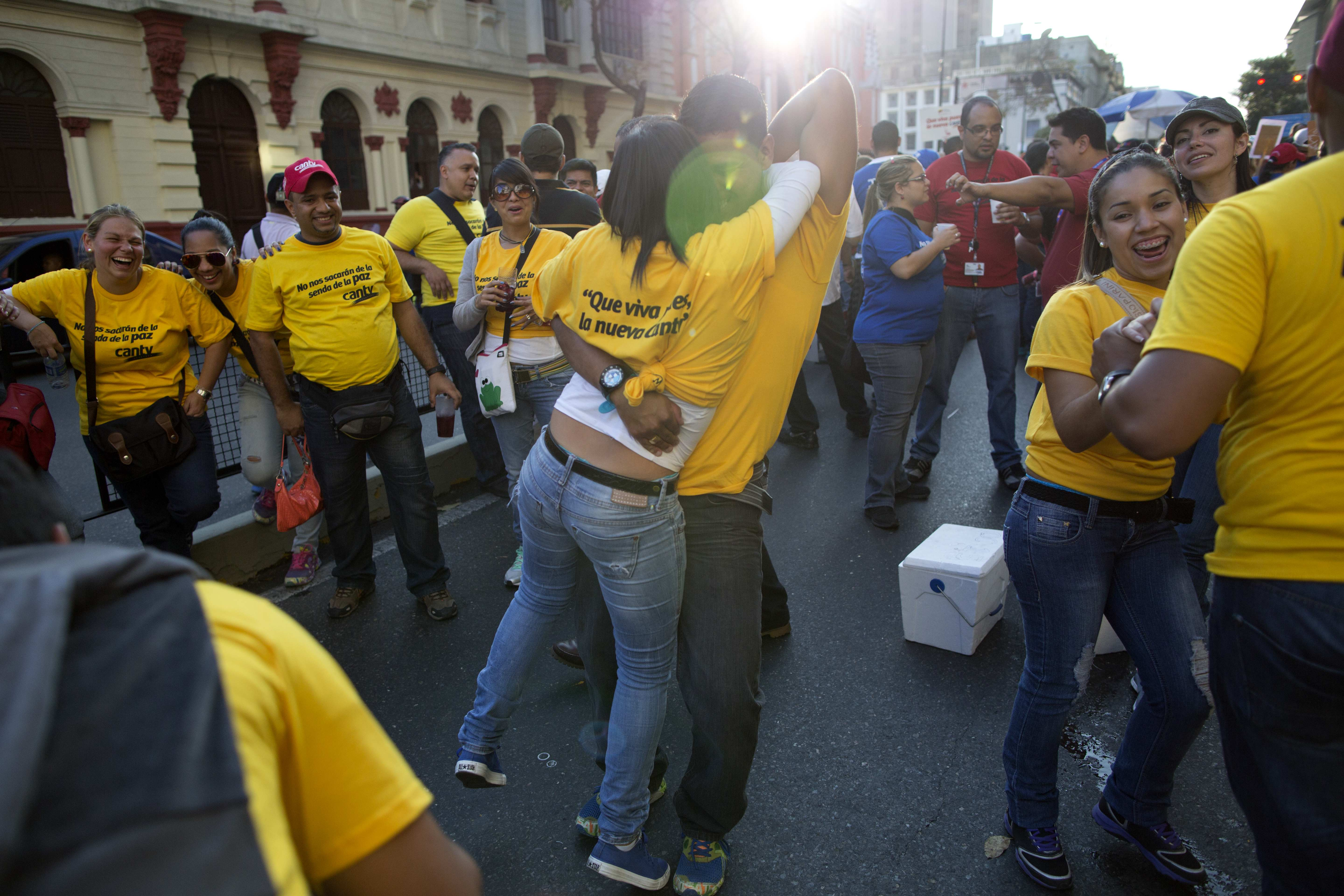 Workers from the National Telecommunications Company CANTV dance during a rally to show support for the government in Caracas, Venezuela, Tuesday, Feb. 25, 2014. (AP Photo/Rodrigo Abd)