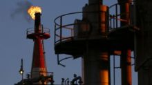 Oil edges up on falling U.S. crude inventories, but supply remains ample