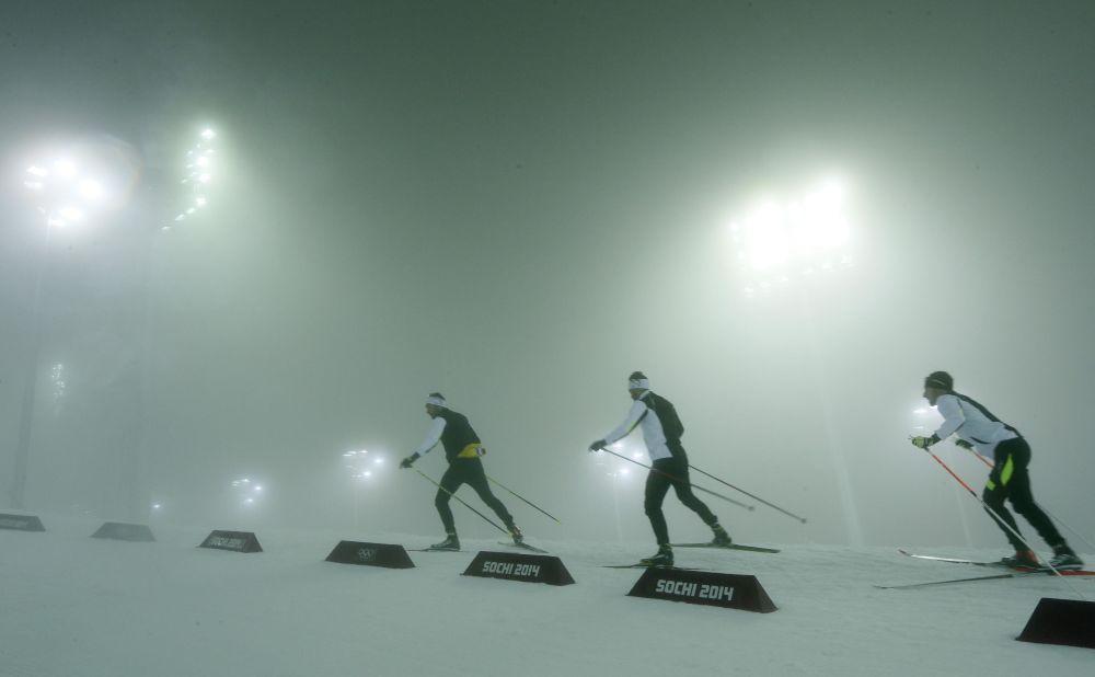 Athletes ski through the stadium after the men's biathlon 15K mass start race was postponed due to fog at the 2014 Winter Olympics, Sunday, Feb. 16, 2014, in Krasnaya Polyana, Russia