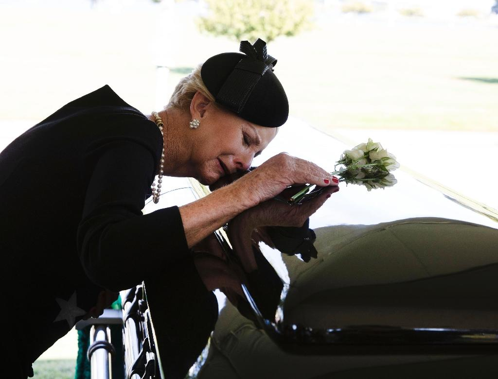 Cindy McCain lays her head on the casket of her husband John McCain during a burial service at the cemetery at the United States Naval Academy (AFP Photo/David Hume Kennerly)