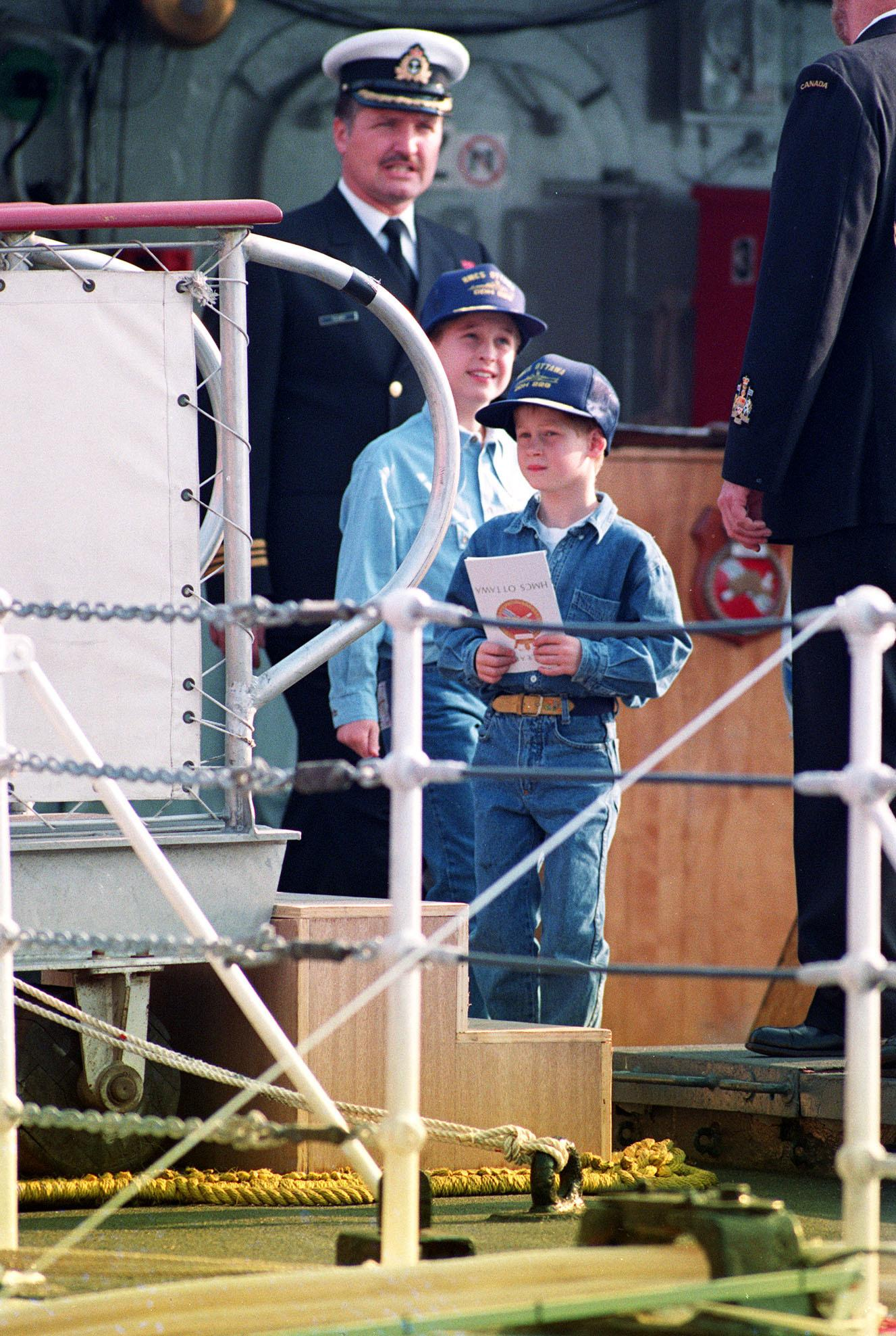 Prince William, 9, and his younger brother, Prince Harry, 7, wear baseball-style caps given to them by the crew of the Canadian frigate HMCS Ottowa as they tour the ship which is moored alongside the Royal Yacht Britannica on the Toronto waterfront.   (Photo by Martin Keene - PA Images/PA Images via Getty Images)