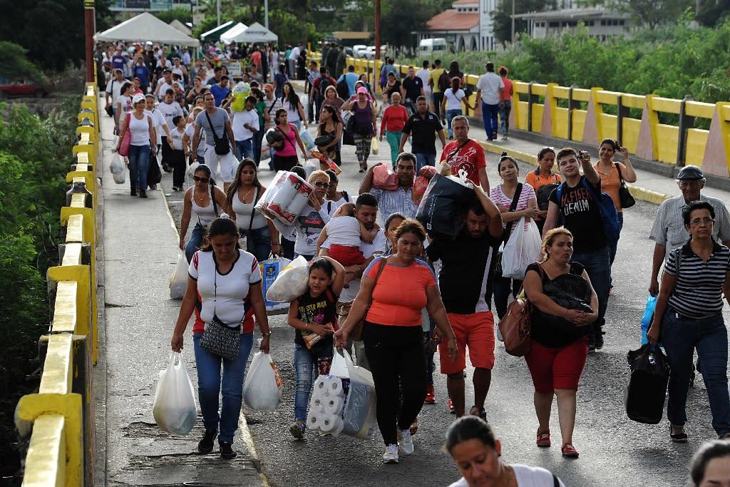 Venezuelans carrying groceries cross the Simon Bolivar bridge from Cucuta in Colombia back to San Antonio de Tachira in Venezuela, on July 10, 2016 (AFP Photo/George Castellanos)
