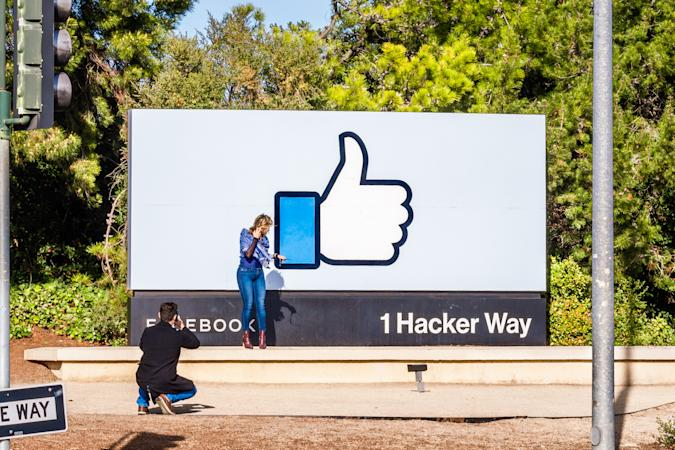 Feb 16, 2020 Menlo Park / CA / USA - Girl posing in front of the Facebook Like Button sign, located at the entrance to the company's main headquarters, Silicon Valley