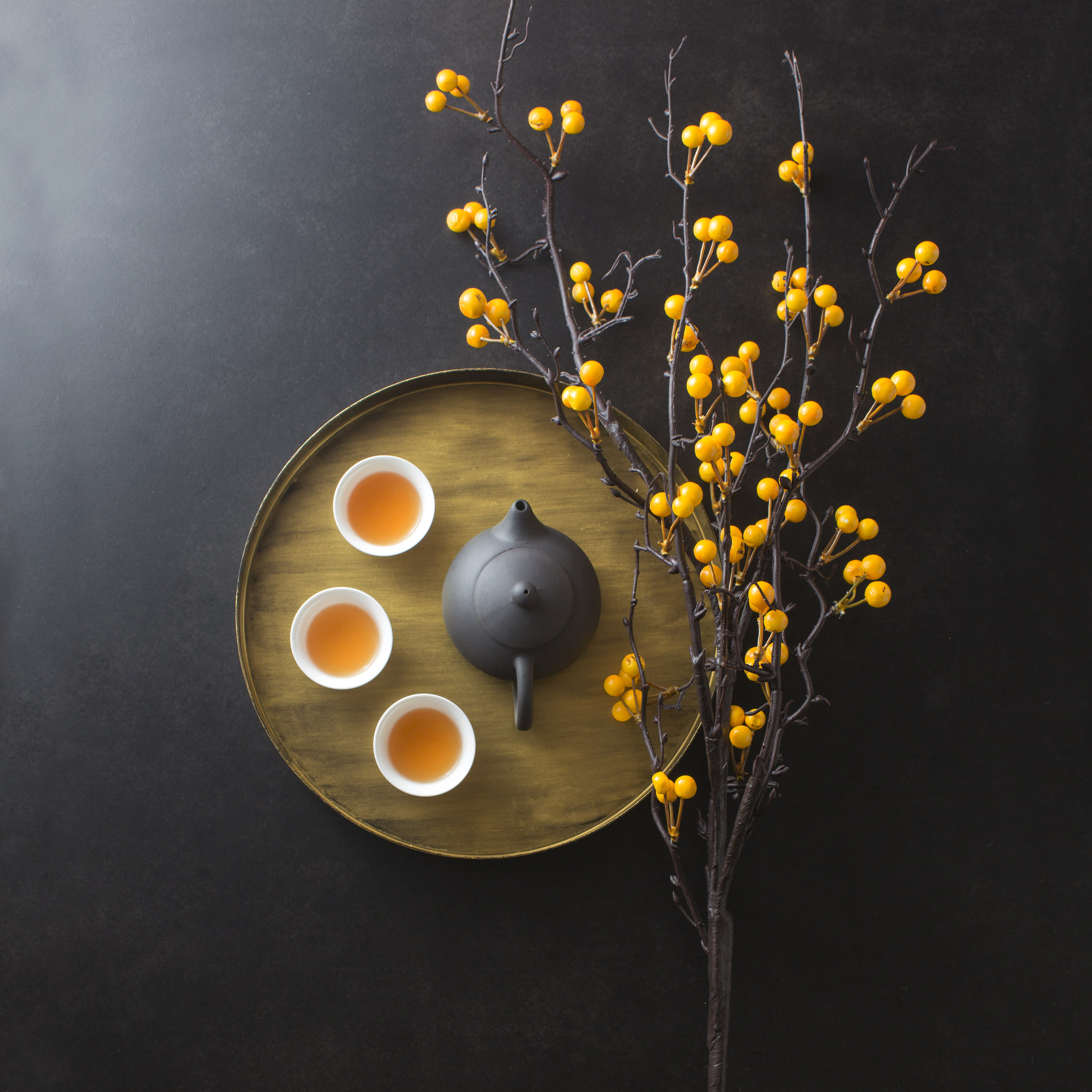 Chinese afternoon tea still life textured moody black background. hand holding tea cup.