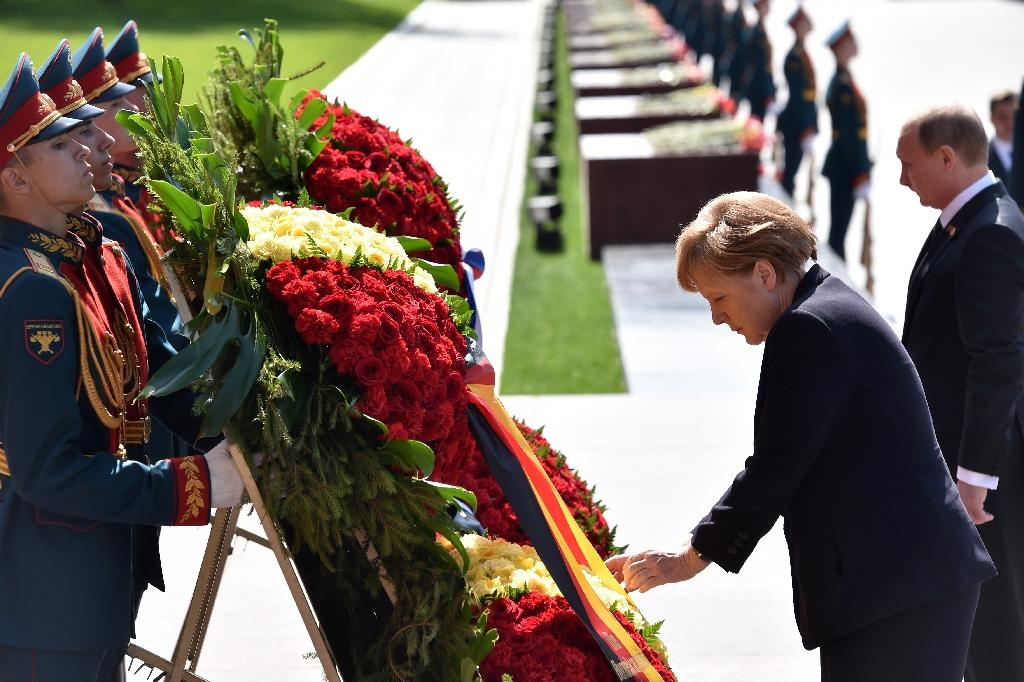 Russian President Vladimir Putin (R) and German Chancellor Angela Merkel (C) take part in a wreath-laying ceremony at the Tomb of the Unknown Soldier by the Kremlin Wall in Moscow on May 10, 2015 (AFP Photo/Kirill Kudryavtsev)