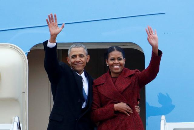 Former President Barack Obama waves with his wife Michelle as they board Special Air Mission 28000, a Boeing 747 which serves as Air Force One, at Joint Base Andrews, Maryland, U.S. Jan. 20, 2017. (Photo: Brendan McDermid/Reuters)
