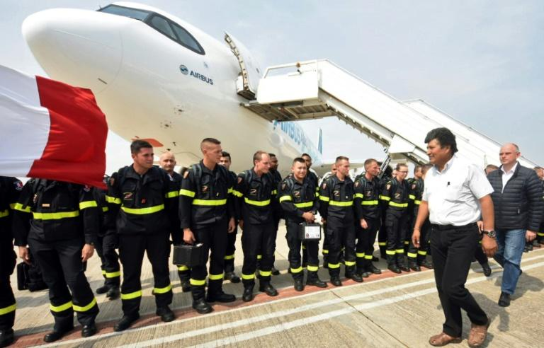 Bolivian President Evo Morales (2-R) and French Ambassador Denis Gaillard review French firefighters upon their arrival in Santa Cruz, Bolivia, to battle wildfires south of the Amazon basin (AFP Photo/Diego VALERO)