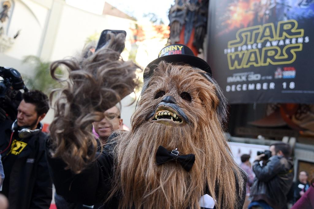 A man in a Chewbacca costume takes a selfie in front of the TCL Chinese Theatre, December 17, 2015 in Hollywood, California (AFP Photo/Robyn Beck)