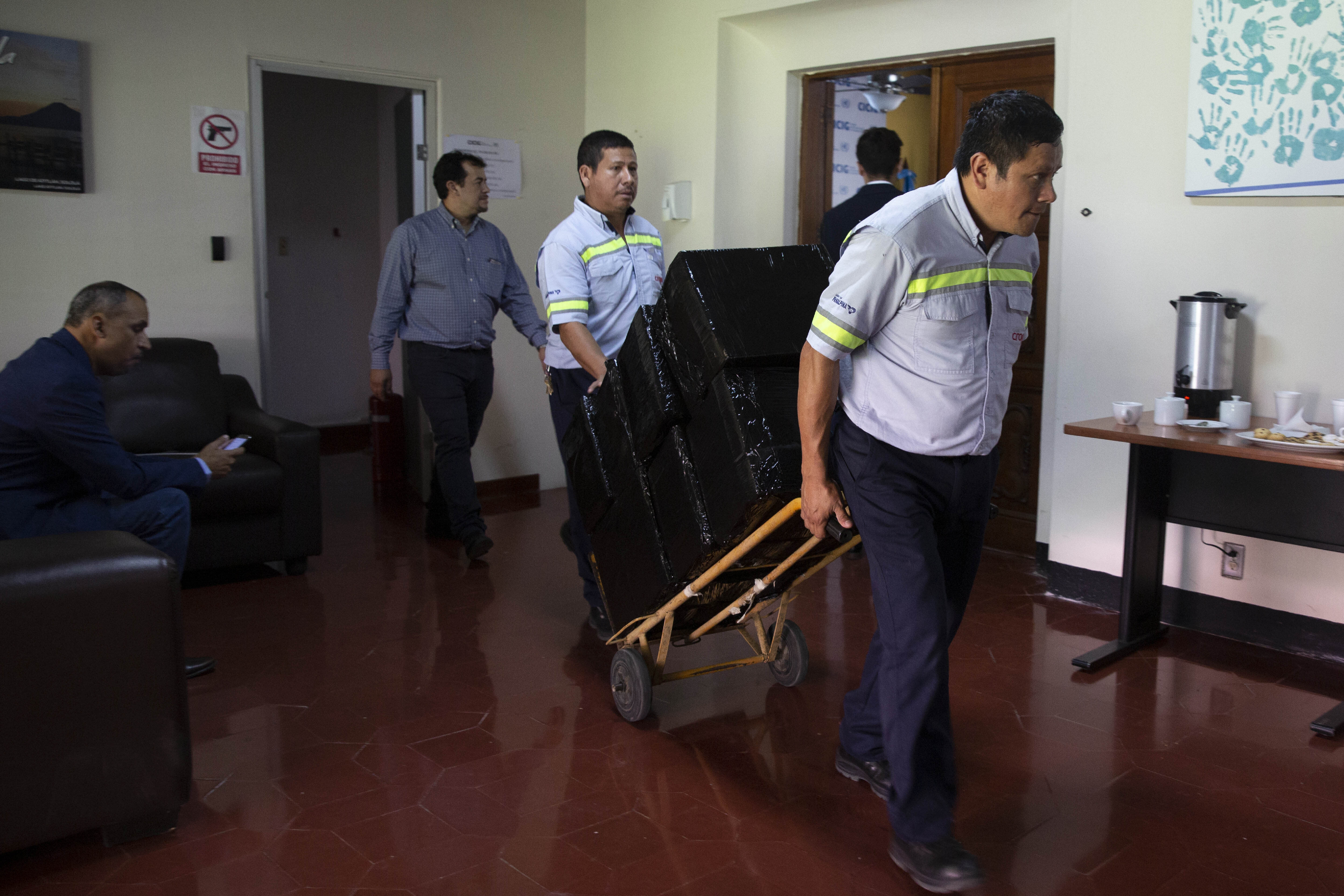 Workers move out items on a dolly as the United Nations International Commission Against Impunity, CICIG, moves out of its headquarters in Guatemala City, Wednesday, Aug. 28, 2019. The UN mission it's closing after 12 years of operation in Guatemala. (AP Photo/Moises Castillo)