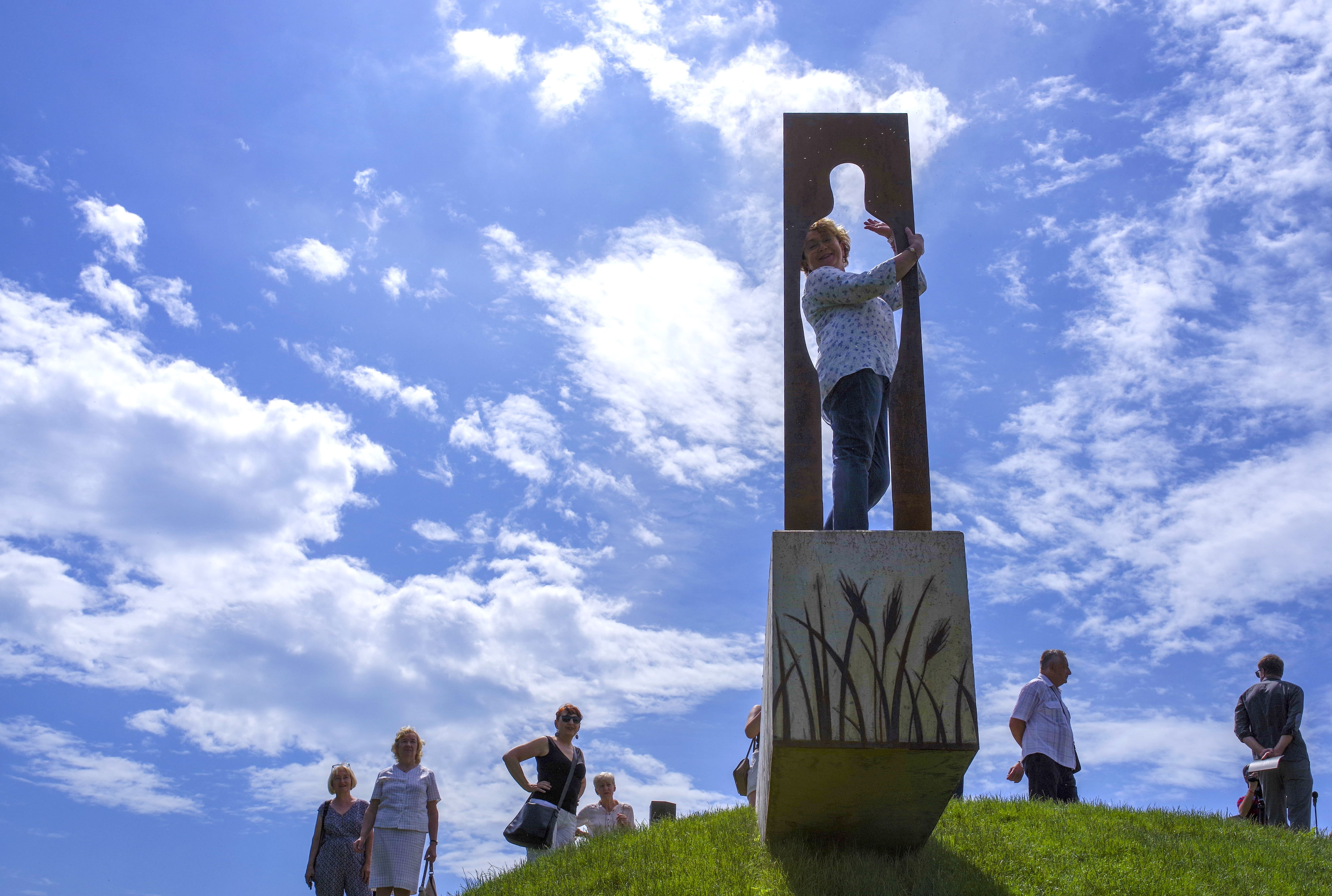 """People look at the new statue of American writer Jerome David Salinger in Paminklas, Lithuania, Friday, June 19, 2020. J.D. Salinger, the American writer best known for his 1951 novel """"The Catcher in the Rye,"""" has been honored with a statue in a rye field, near the Lithuanian village where his ancestors lived. (AP Photo/Vladas Sciavinskas)"""