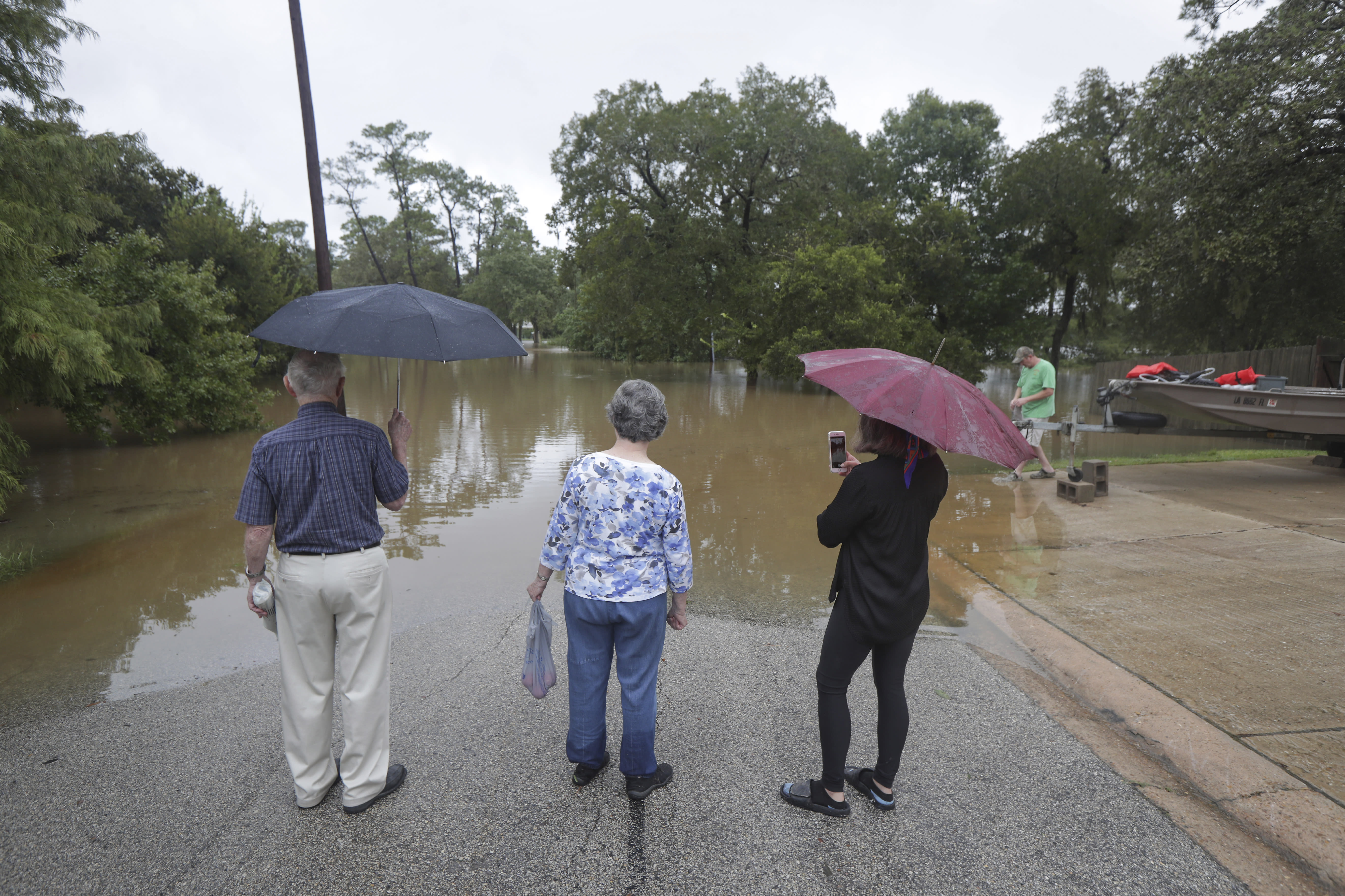 Local residents Harold and Carolyn Benson (l-r) along with Tara Richardson view the submerged Mary Xing bridge over Marys Creek that leads into Clear Creek as Tropical Storm Beta rainfall trained over the area Tuesday, Sept. 22, 2020, in Friendswood, Texas (Steve Gonzales/Houston Chronicle via AP)