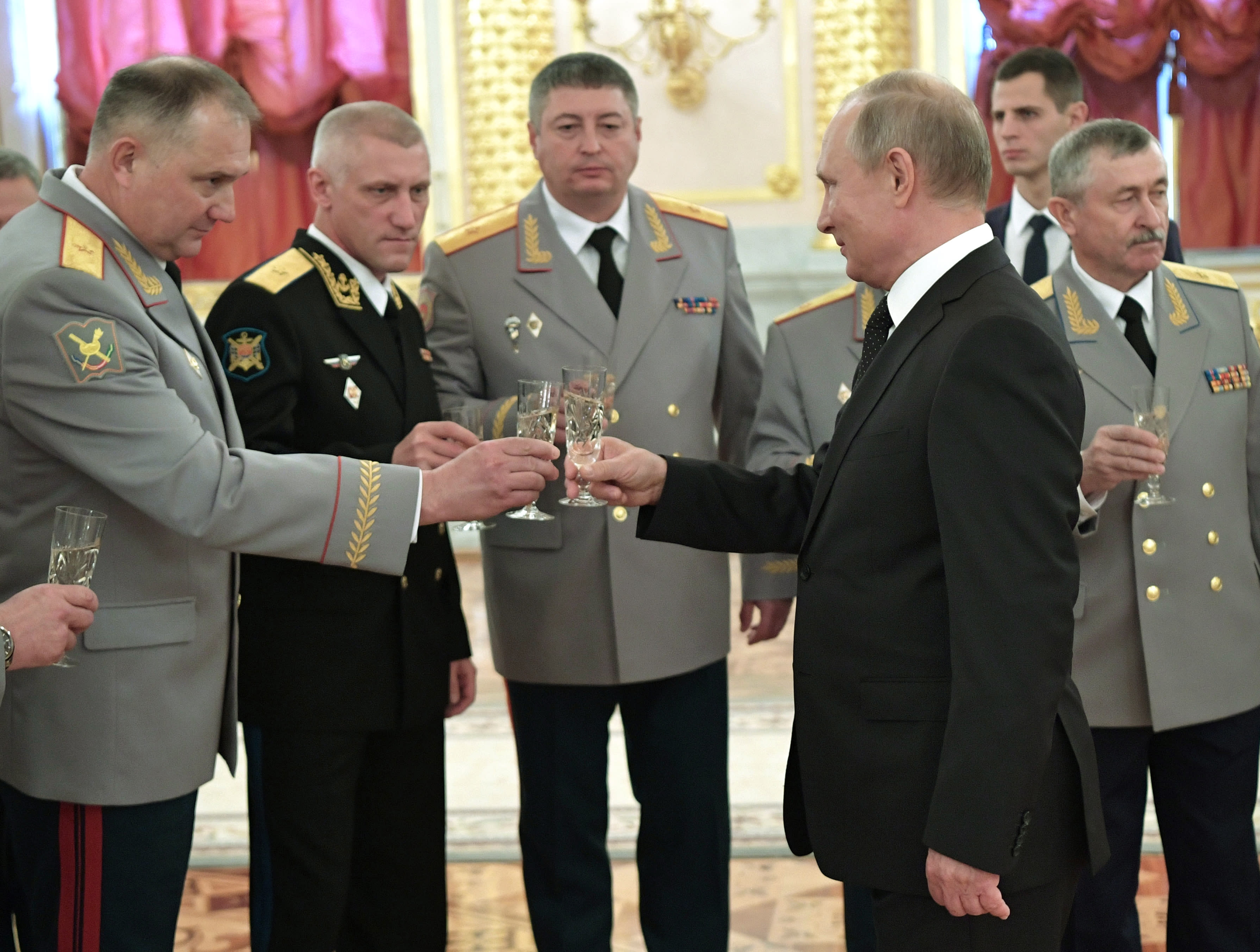 Russian President Vladimir Putin, foreground right, toasts with top military officers and law enforcement officials in the Kremlin in Moscow, Russia, Thursday, Oct. 25, 2018. Putin said that Russia has adhered to its obligations in the arms control sphere, but noted that Russian arsenals will be modernized to ensure protection from any potential threats. (Alexei Nikolsky, Sputnik, Kremlin Pool Photo via AP)