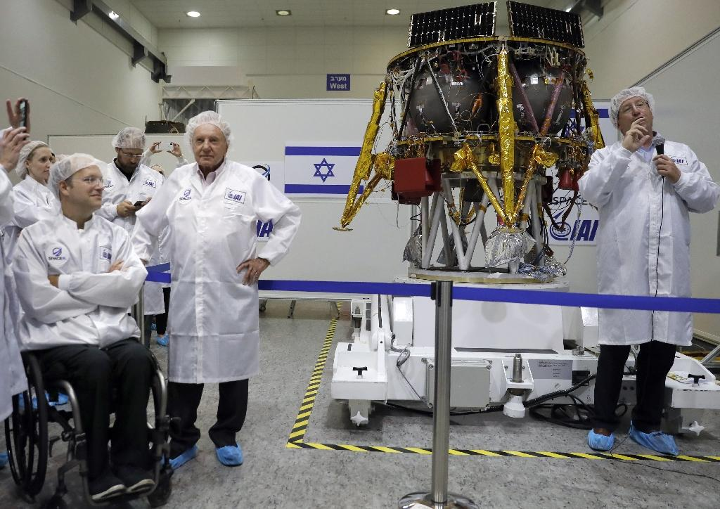 Israeli Aerospace Industries director of Space division Opher Doron (R) and billionaire investor Morris Kahn (2nd-R) present a spacecraft during a press conference to announce its launch to the moon, in Yehud, central Israel (AFP Photo/THOMAS COEX)