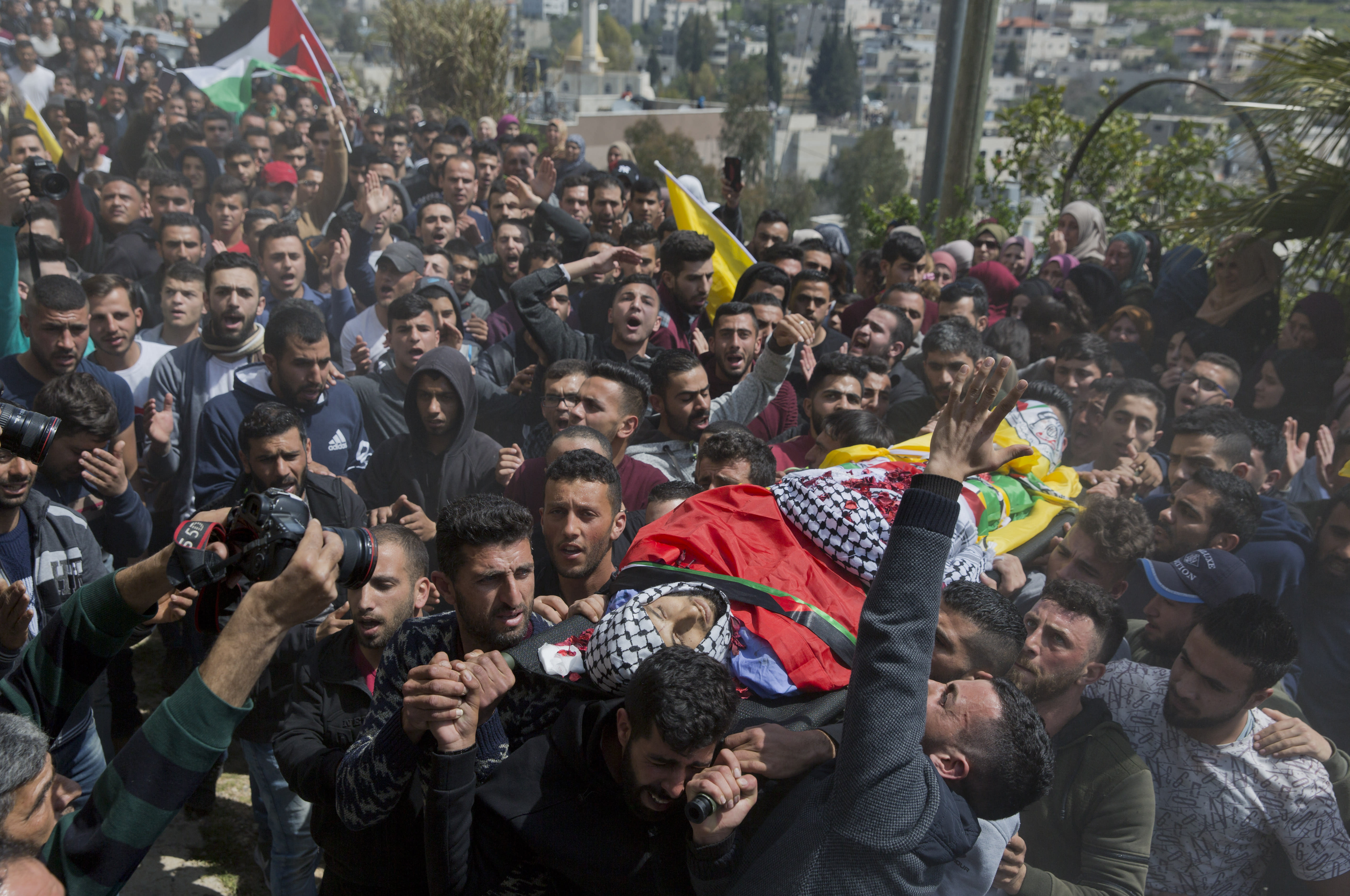 FILE - In this March 21, 2019 file photo, Palestinian mourners carry the body of Ahmad Manasra, during his funeral in the West Bank village of Wad Fokin, near Bethlehem. In August 2020, Israeli military prosecutors offered three months of community service to a soldier who shot and killed Manasra, an unarmed Palestinian man who exited his vehicle to assist a second motorist who had also been shot -- in a case that has drawn renewed attention to a justice system that Palestinians and human rights activists say has created an atmosphere of impunity. The deal is now being reviewed by the Israeli Supreme Court. (AP Photo/Nasser Nasser, File)