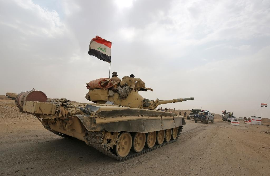 Iraqi soldiers drive Russian-made T-72 tank as Iraqi forces advance towards the city of al-Sharqat, north of Baghdad, on September 20, 2017