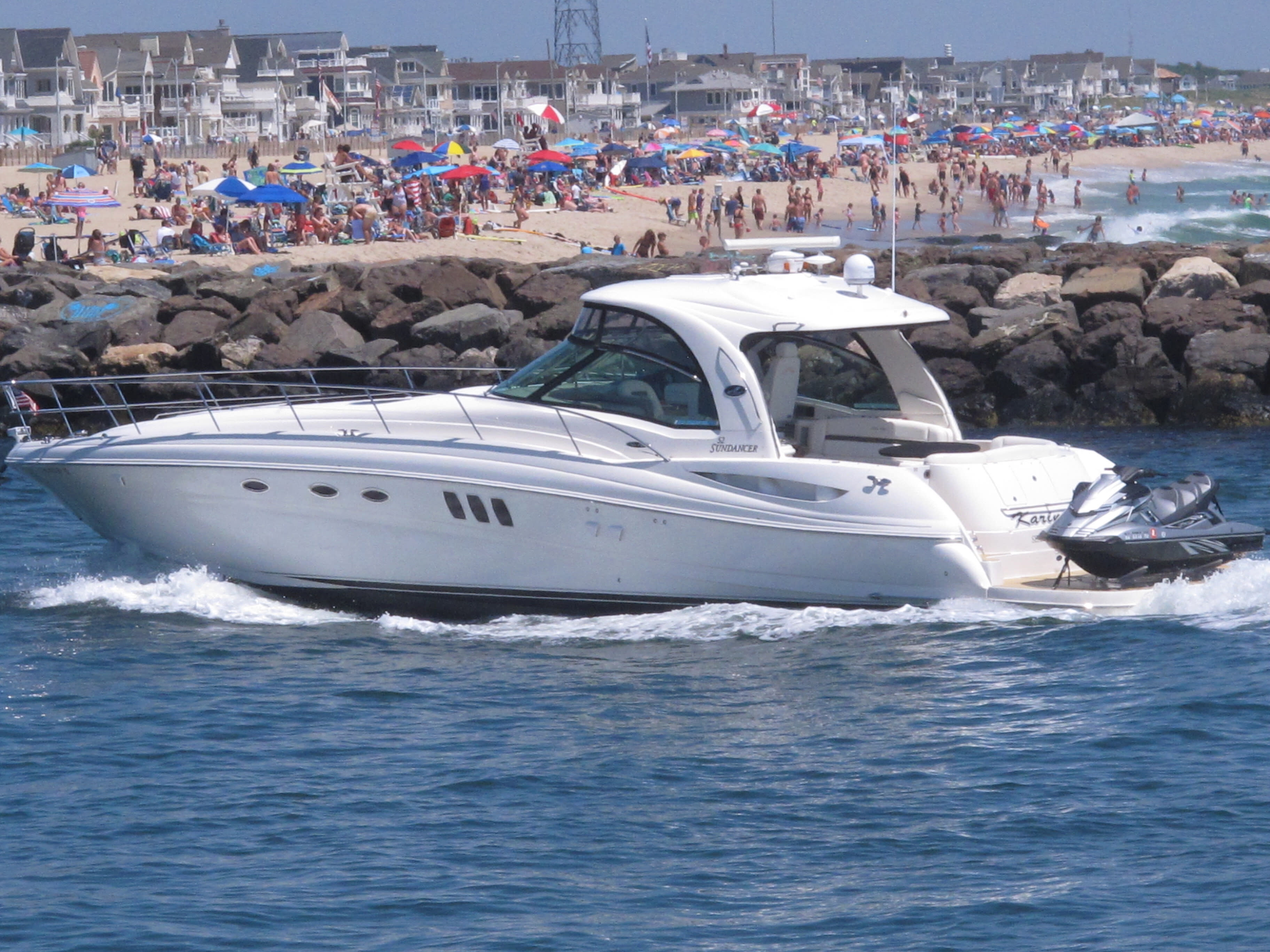 A yacht cruises through the Manasquan Inlet as a large crowd fills the beach in Manasquan, N.J. on June 28, 2020. With large crowds expected at the Jersey Shore for the July Fourth weekend, some are worried that a failure to heed mask-wearing and social distancing protocols could accelerate the spread of the coronavirus. (AP Photo/Wayne Parry)
