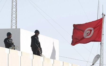 Tunisian policemen patrol the roof of a police station, after Monday's attack by Islamist fighters on an army and police barracks in the town of Ben Guerdan