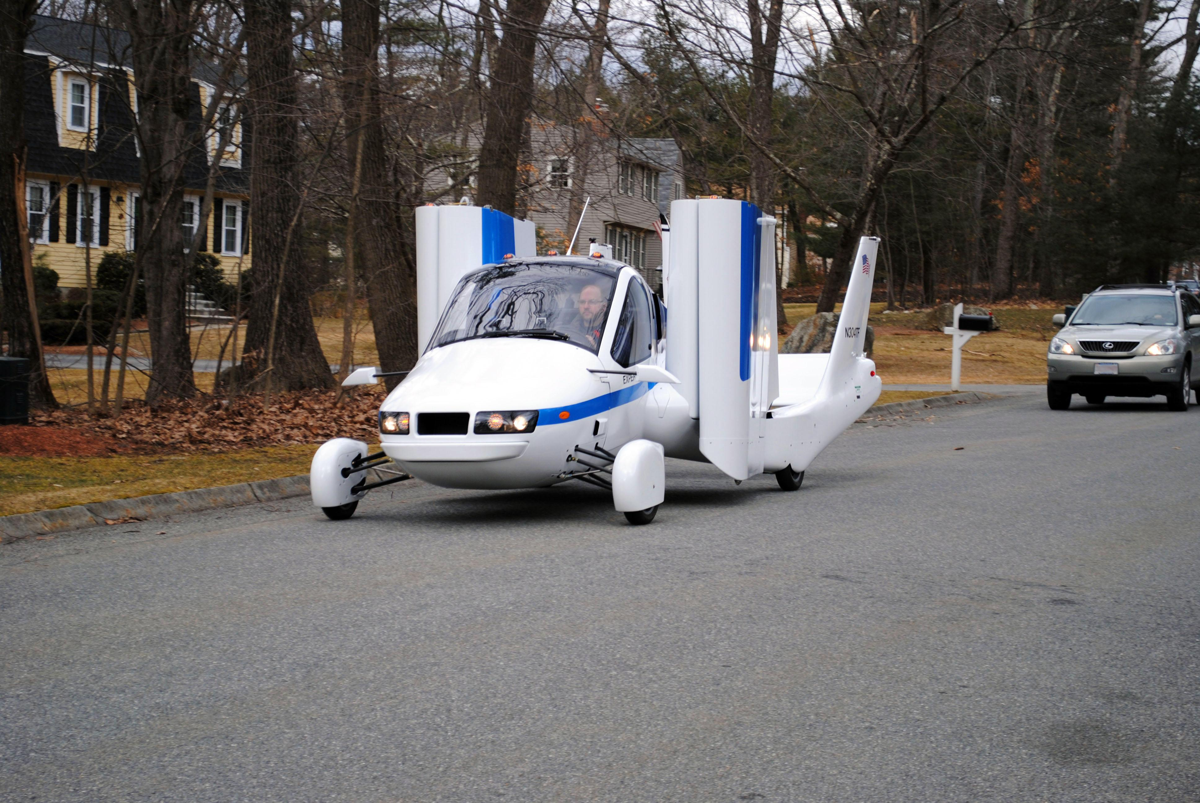 In this undated photo provided by Terrafugia Inc., the company's prototype flying car, dubbed the Transition, travels down a street with its wings folded. The vehicle has two seats, four wheels and wings that fold up so it can be driven like a car, and flew at 1,400 feet for eight minutes during its test flight on March 23, 2012. Commercial jets fly at 35,000 feet. (AP Photo/Terrafugia.com) MANDATORY CREDIT