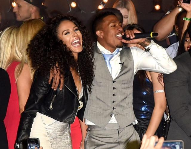 PHOENIX, AZ - JANUARY 31: Miss Guam Brittany Bell and actor/singer Nick Cannon (C) perform onstage during the Maxim Party with Johnnie Walker, Timex, Dodge, Hugo Boss, Dos Equis, Buffalo Jeans, Tabasco and popchips on January 31, 2015 in Phoenix, Arizona. (Photo by Jason Merritt/Getty Images for Maxim)