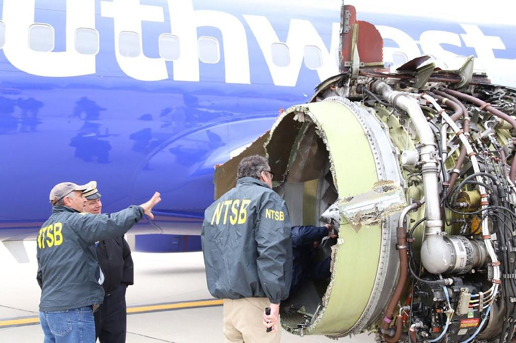 National Transportation Safety Board investigators examining damage to the engine of a Southwest Airlines plane after a midair explosion April 17 that sent shrapnel through a window, causing the death of a passenger (AFP Photo/Handout)