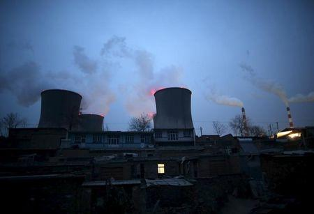 Chimneys of coal-fired power plant are seen next to residential houses in the night in Shijiazhuang