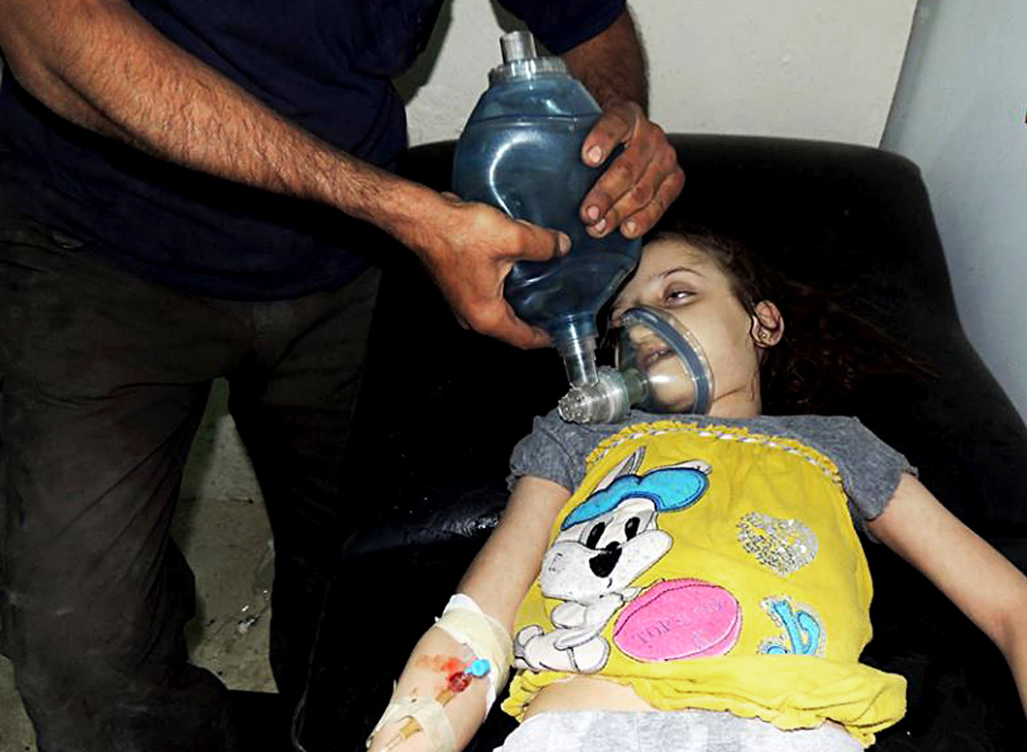 FILE - In this Aug. 21, 2013, file citizen journalism image provided by the Local Committee of Arbeen which has been authenticated based on its contents and other AP reporting, a Syrian girl receives treatment at a makeshift hospital in Arbeen town, Damascus, Syria. The early-morning barrage against rebel-held areas around the the Syrian capital Damascus immediately seemed different: The rockets made a strange, whistling noise. Seconds after one hit near his home, Qusai Zakarya says he couldn't breathe, and he desperately punched himself in the chest to get air. Hundreds of suffocating, twitching victims flooded into hospitals. Others were later found dead in their homes, towels still on their faces from their last moments trying to protect themselves from gas. Doctors and survivors recount scenes of horror from the alleged chemical attack a week ago. (AP Photo/Local Committee of Arbeen, File)