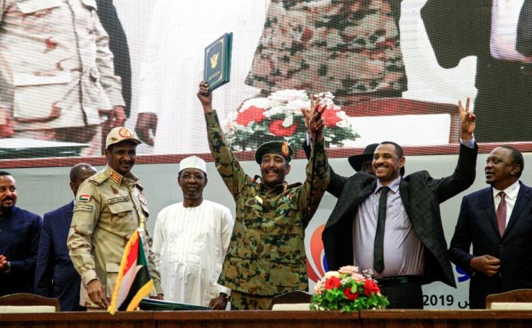 "Sudanese protest leader Ahmad Rabie (2nd-R), flashes the victory gesture alongside General Abdel Fattah al-Burhan (C), head of the ruling military council, during a ceremony where they signed a ""constitutional declaration"" (AFP Photo/Ebrahim HAMID)"