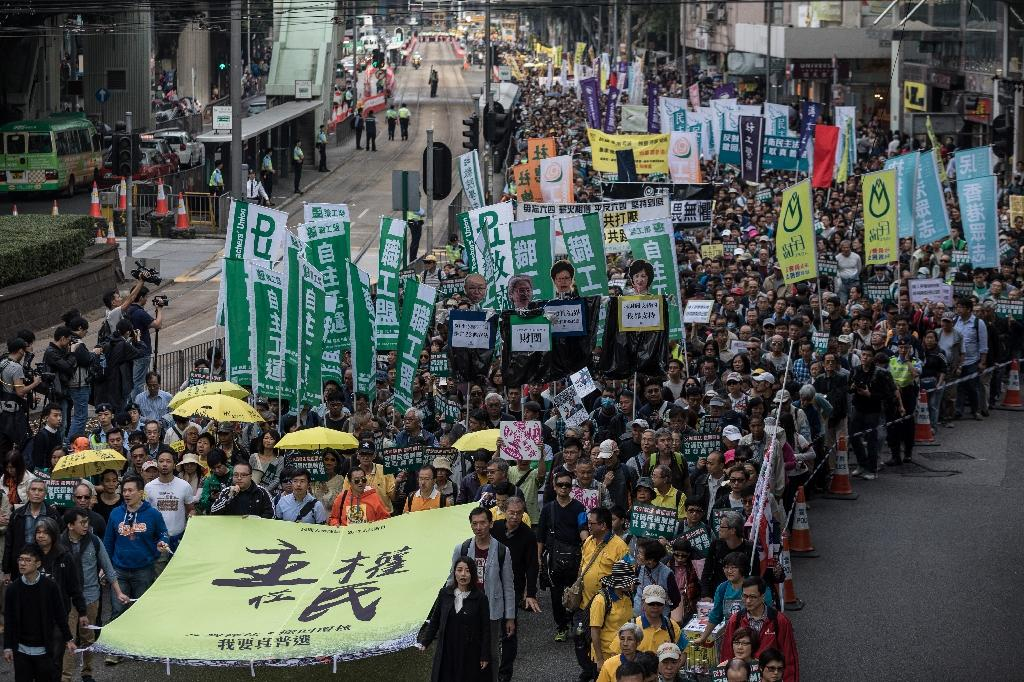 """Protesters including pro-democracy lawmakers Lau Siu-lai (bottom C), Edward Yiu (behind Lau) and Nathan Law (bottom L) carry a banner reading """"Sovereignty belongs to the people!"""" during a New Year's Day rally in Hong Kong on January 1, 2017"""
