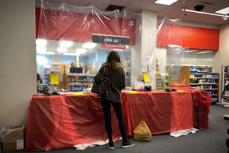FILE PHOTO: Woman waits behind a sheet of protective plastic at the pharmacist's counter at a CVS Pharmacy during the outbreak of coronavirus disease (COVID-19) in New York