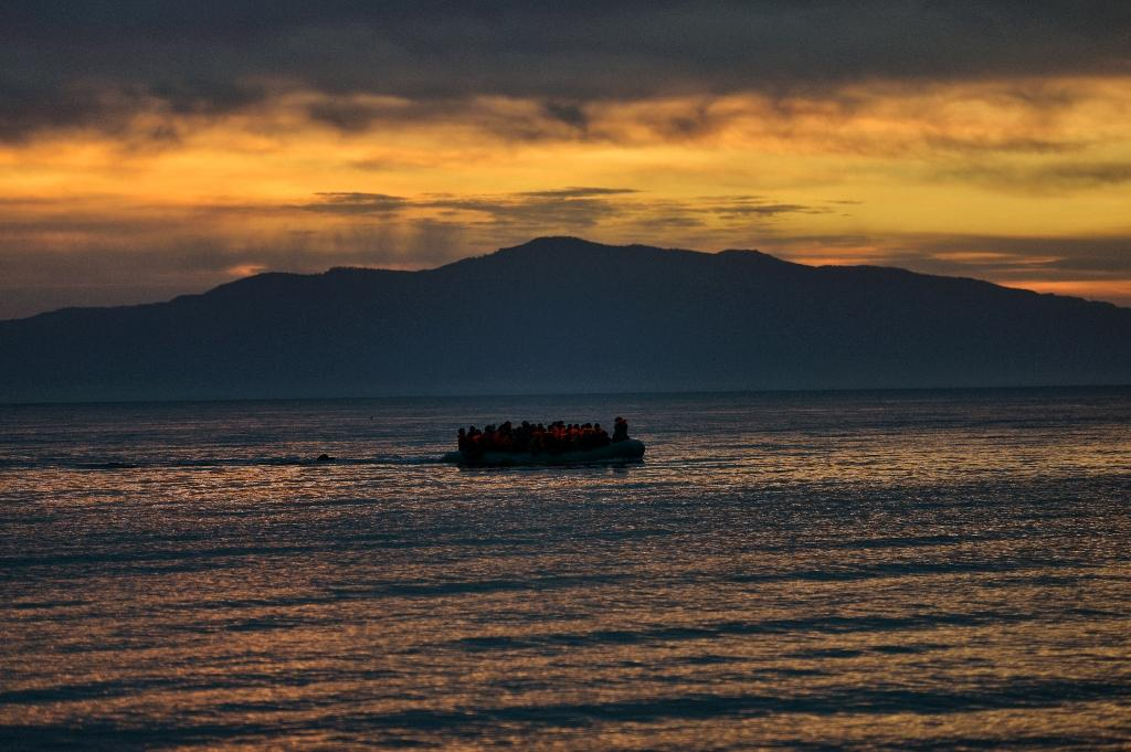 Refugees and migrants massed onto an inflatable boat reach the island of Lesbos, after crossing the Aegean sea from Turkey on February 17, 2016 (AFP Photo/Aris Messinis )