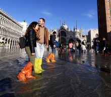 As tides rise, flooded Venice awash with colourful plastic boots