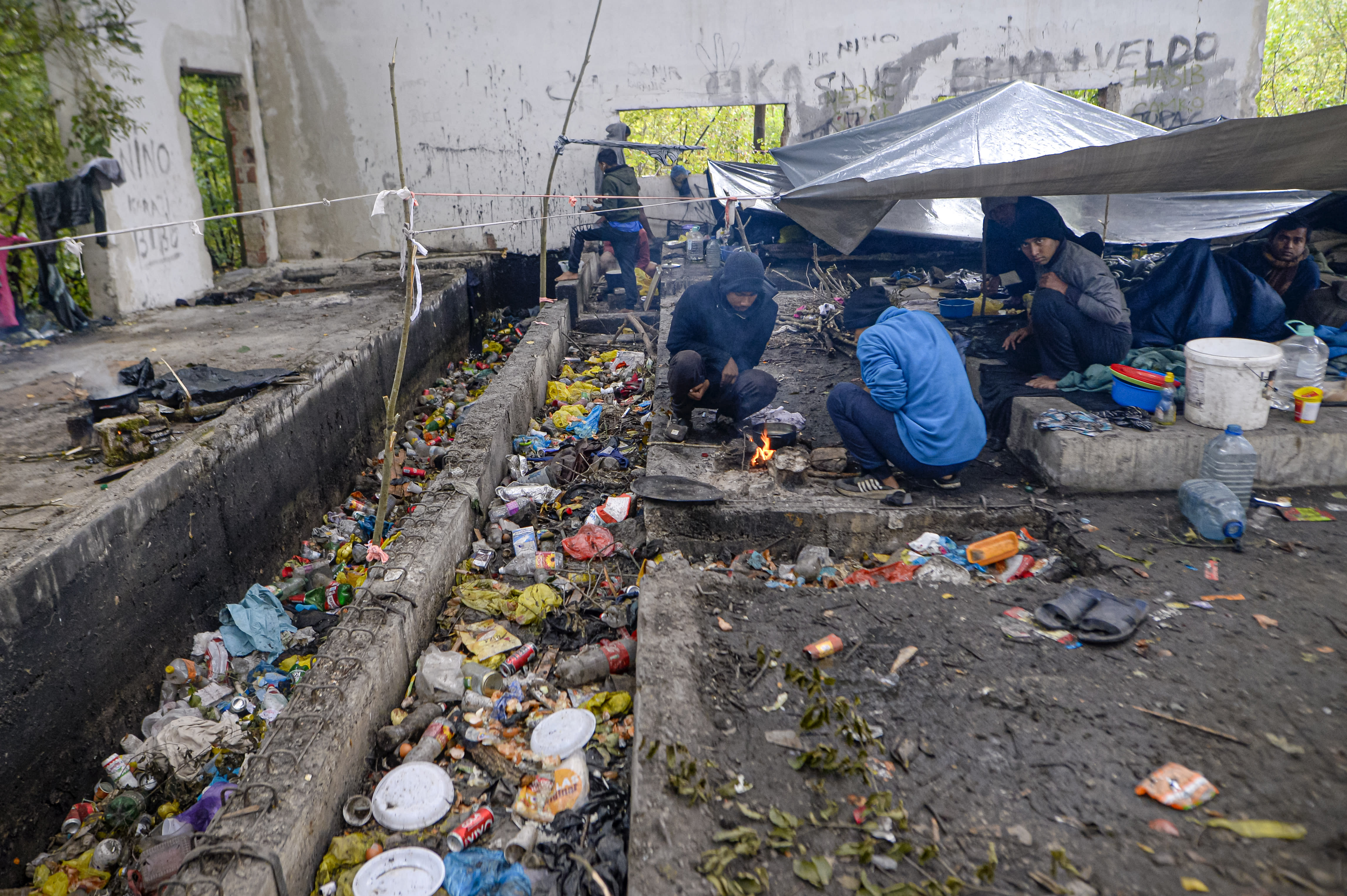 Migrants cook on an open fire in an abandoned factory outside Velika Kladusa, Bosnia, Saturday, Sept. 26, 2020. Remote woods, abandoned run-down buildings and roadsides on the fringes of northwestern Bosnian towns are steadily filling with makeshift camps where migrants from the Middle East, Asia and North Africa are bracing for more misery as autumn's chill and rains set it. (AP Photo/Kemal Softic)