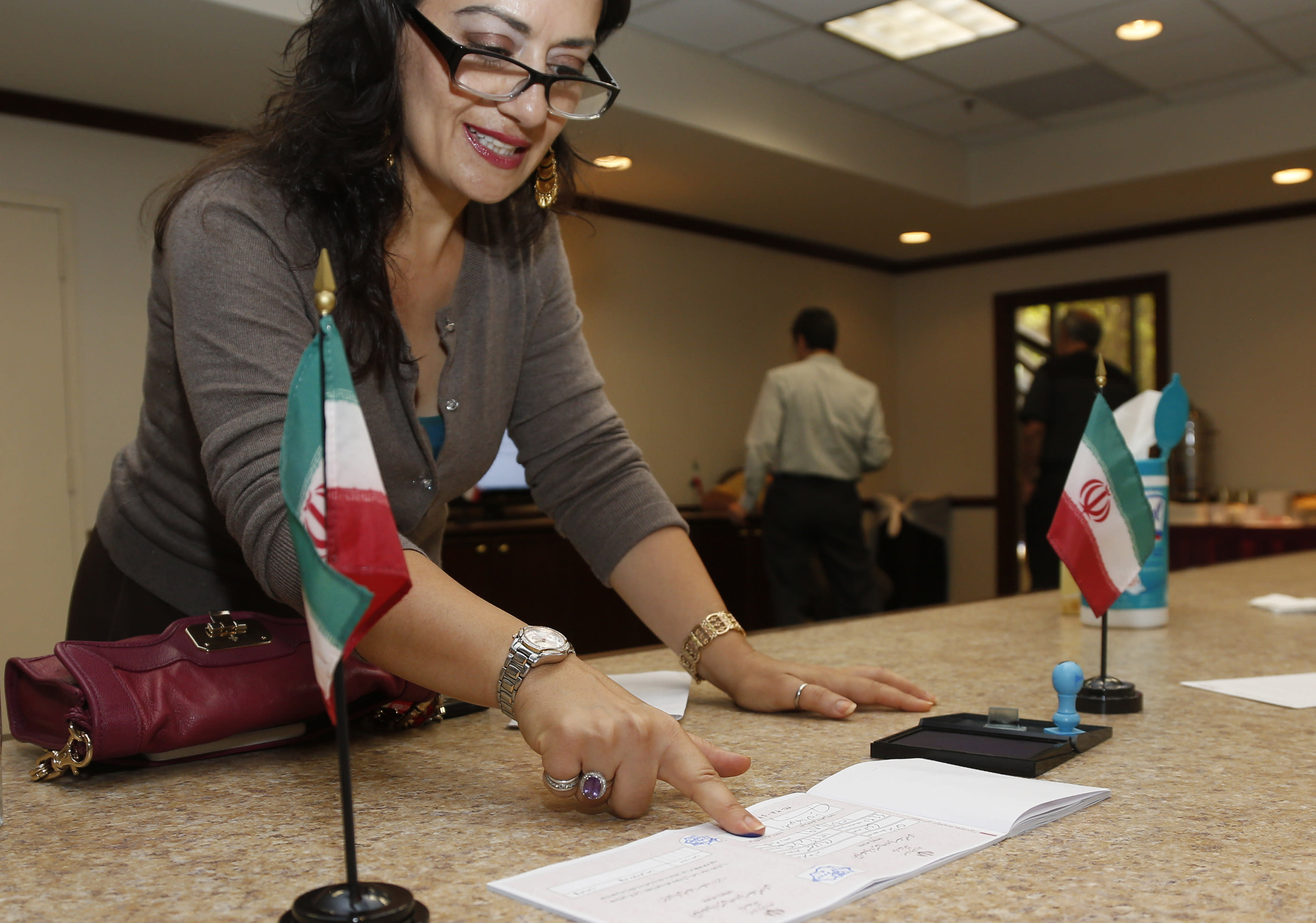 Marjan Seirofi-Pour, of Norman, Okla., presses her finger to her ballot as she votes in the Iranian Presidential election in Oklahoma City, Friday, June 14, 2013. Iranian-Americans and expatriates cast ballots Friday in polling places across the United States, joining their countrymen half a world away in selecting the next Iranian president. (AP Photo/Sue Ogrocki)