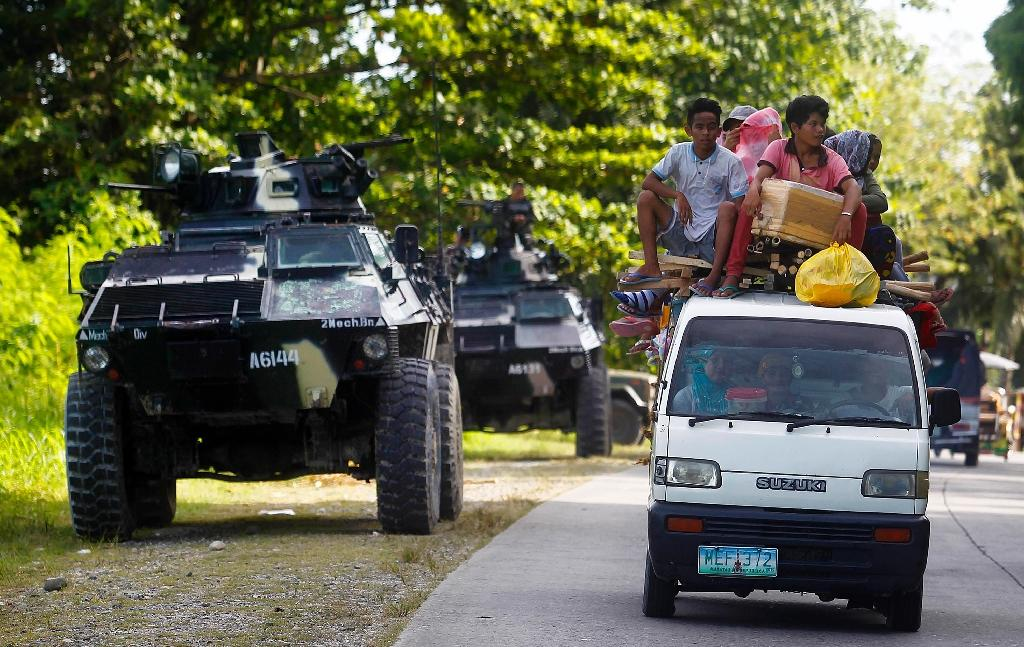 Soldiers in armoured personnel carriers stand guard in Kauran, Ampatuan in the southern Philippines province of Maguindanao