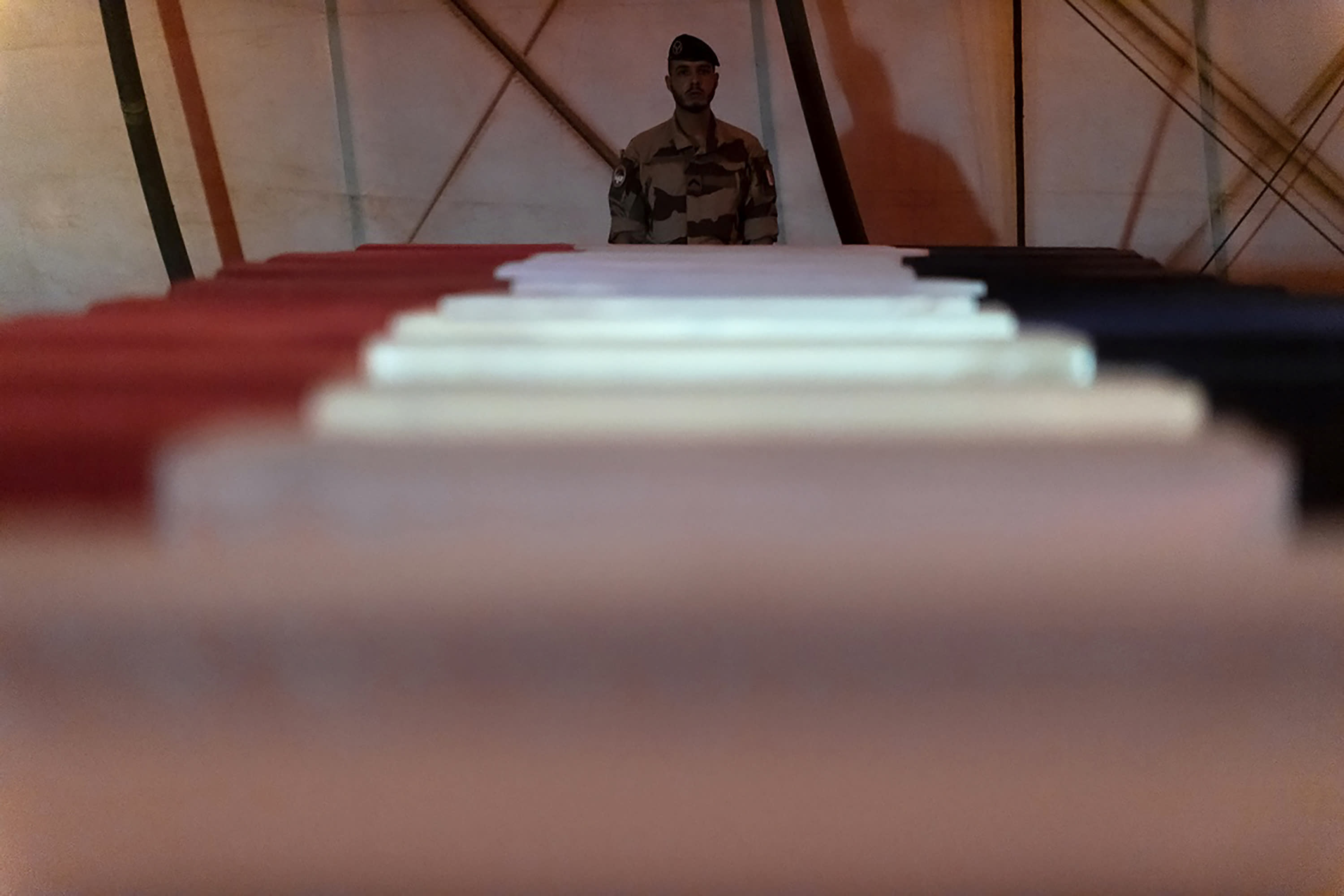 In this Wednesday, Nov. 27, 2019, photo provided by French Defense Communication and Audiovisual Department (ECPAD), a soldier stands guard by the coffins of the 13 French soldiers, in Gao, Mali. France's Defense Minister Florence Parly arrived in northern Mali on Wednesday after a helicopter collision killed 13 French soldiers fighting Islamic State group-linked extremists, while some in the West African country debated France's military presence. (Thomas Peudeleux/ECPAD via AP)