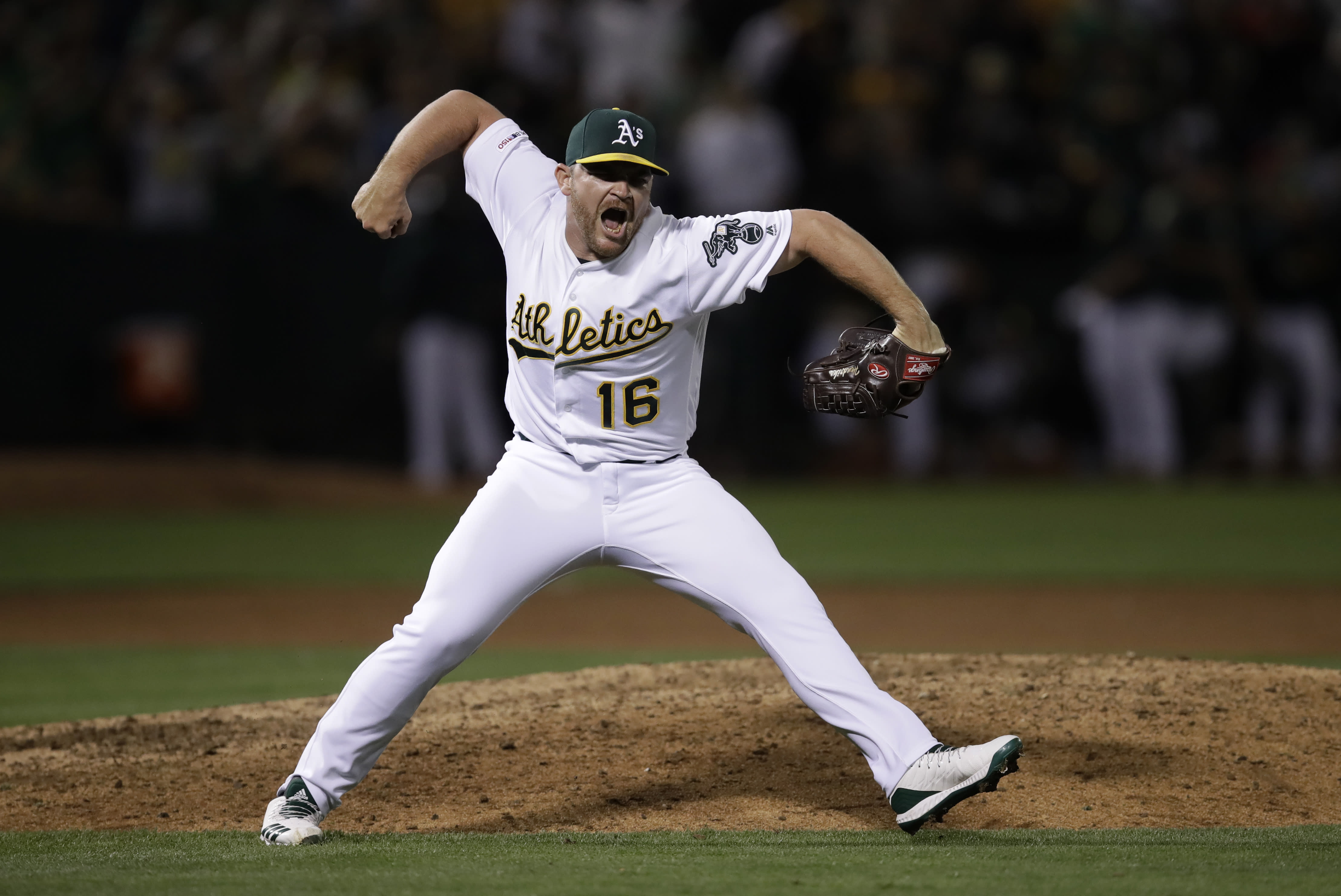 FILE - In this Aug. 21, 2019, file photo, Oakland Athletics pitcher Liam Hendriks celebrates as the final out is made in the team's baseball game against the New York Yankees, in Oakland, Calif. Manager Bob Melvin and the Oakland Athletics have put their faith in Hendriks to finish games as a reliable ninth-inning option night after night. Never one to stick with traditional methods and frustrated with himself last year in Triple-A, Hendriks searched for a way to transform his mental approach. This good-natured Aussie was in need of an attitude shift. And an energy healer named Rubi Rios sure provided a nice assist in his transformation process. (AP Photo/Ben Margot, File)