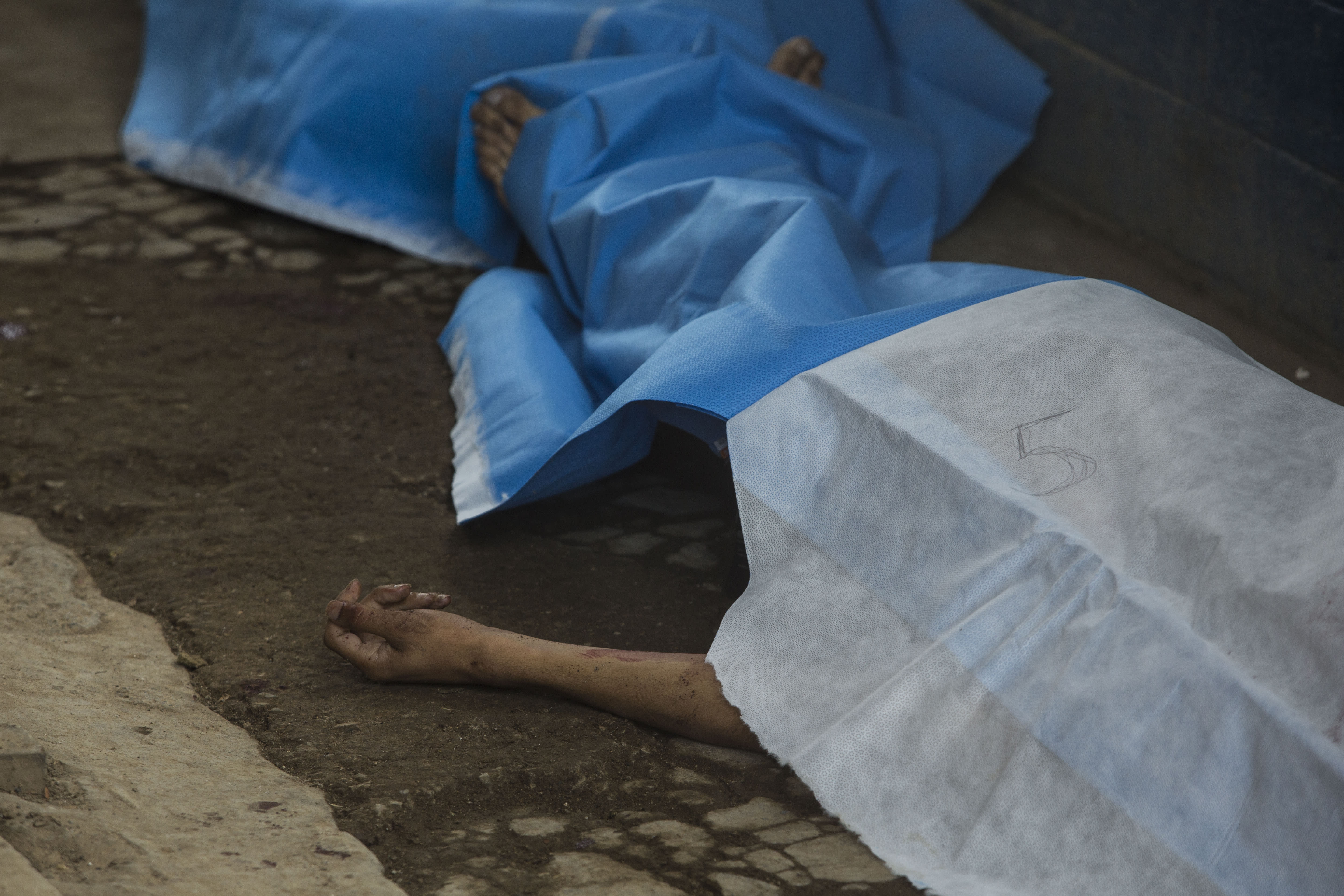 Covered bodies lie inside the entrance area of the Pavon Rehabilitation Model Farm after a shooting inside the jail in Fraijanes, Guatemala, Tuesday, May 7, 2019. Gunfire during a riot in a Guatemala prison Tuesday left at least seven inmates dead and 10 wounded, authorities said. (AP Photo/Oliver De Ros)