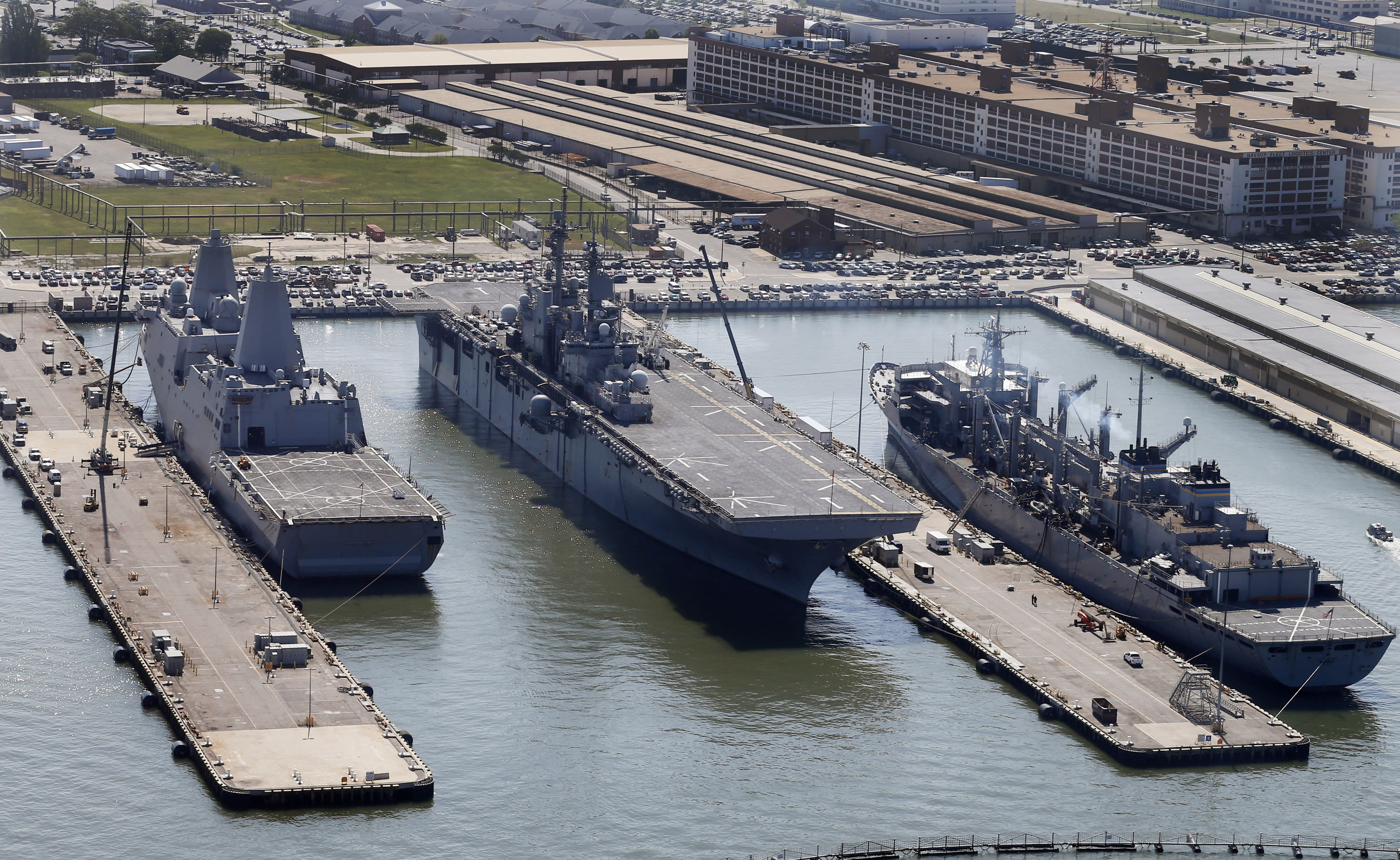 FILE - In this April 27, 2016, file photo, the amphibious assault ship USS Wasp (LHD-1), center, sits pier side along with support ships at Naval Station Norfolk in Norfolk, Va. The U.S. Navy amphibious assault ship USS Wasp arrived in Subic Bay, the Philippines, Saturday, March 30, 2019, with its complement of Marines and F-35 Lightning II fighter jets in preparation for joint exercises with the Philippines.(AP Photo/Steve Helber, File)