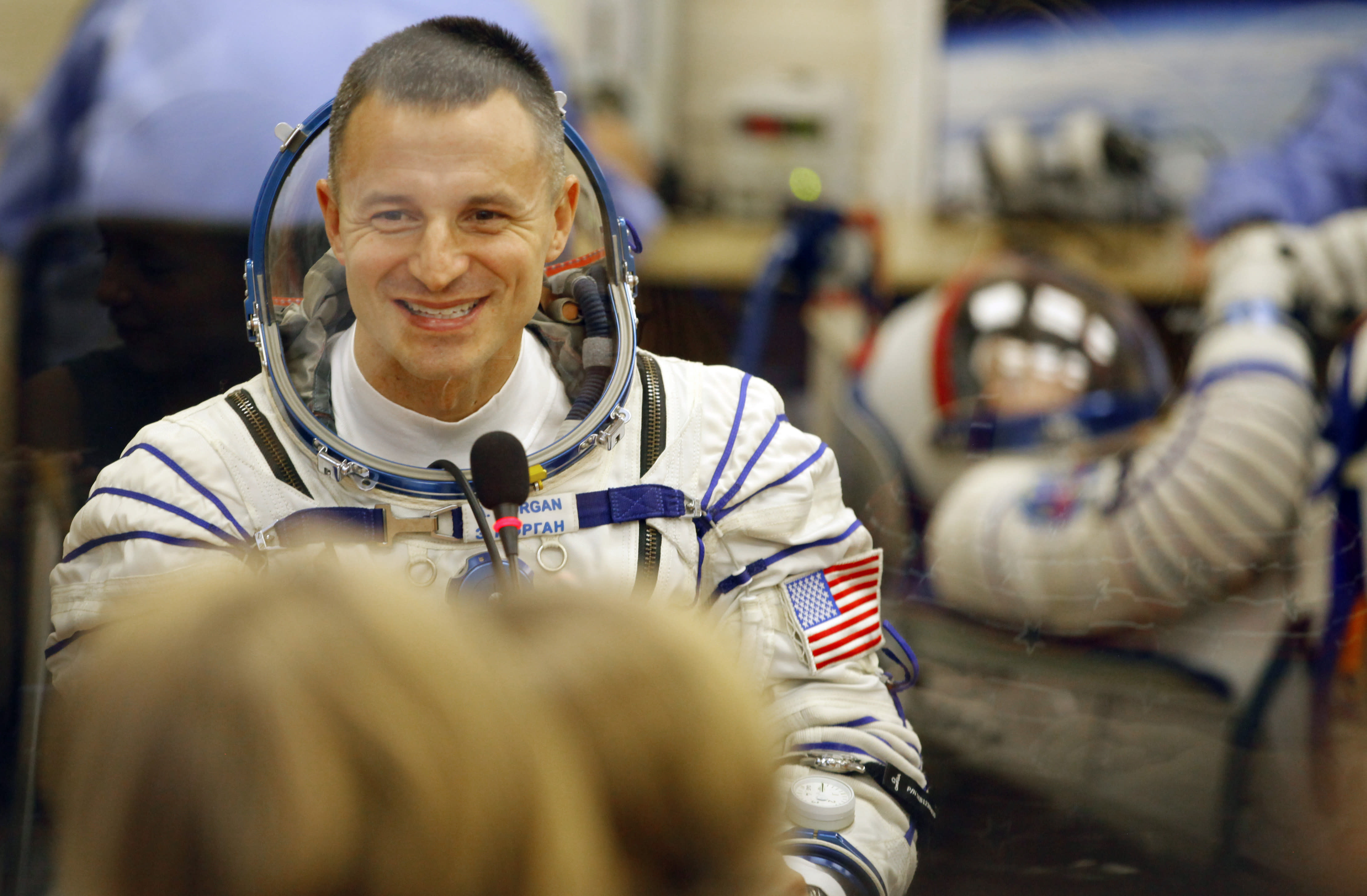U.S. astronaut Andrew Morgan, speaks with his relatives through the safety glass prior the launch of Soyuz-FG rocket at the Russian leased Baikonur cosmodrome, Kazakhstan, Saturday, July 20, 2019. (AP Photo/Dmitri Lovetsky)