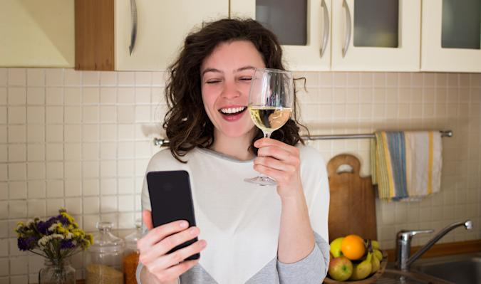 Happy young smiling caucasian woman making video call with smartphone at kitchen. Best friends drinking white wine and toasting. Video conference party online meeting with family. Stay home.Isolation