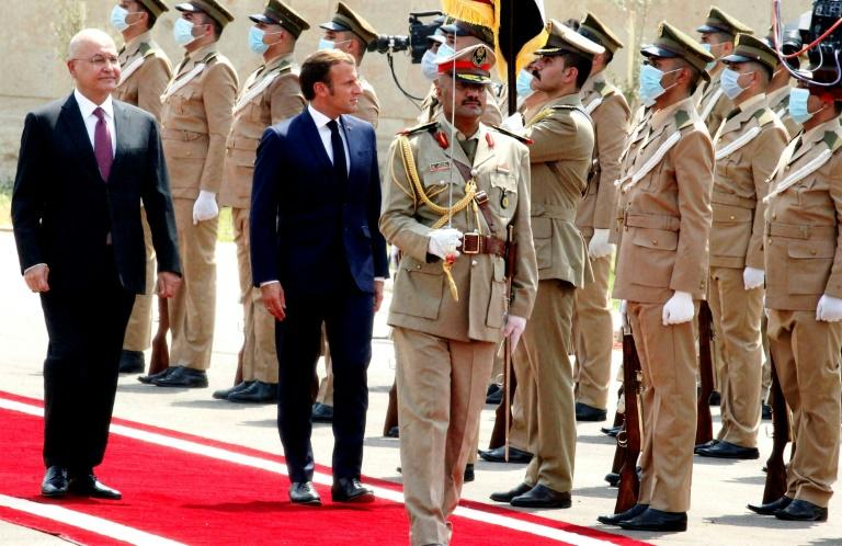 Iraq's President Barham Saleh (L), who is warning of risks to his country, inspects an honor guard as he welcomes French President Emmanuel Macron (R) on September 2, 2020