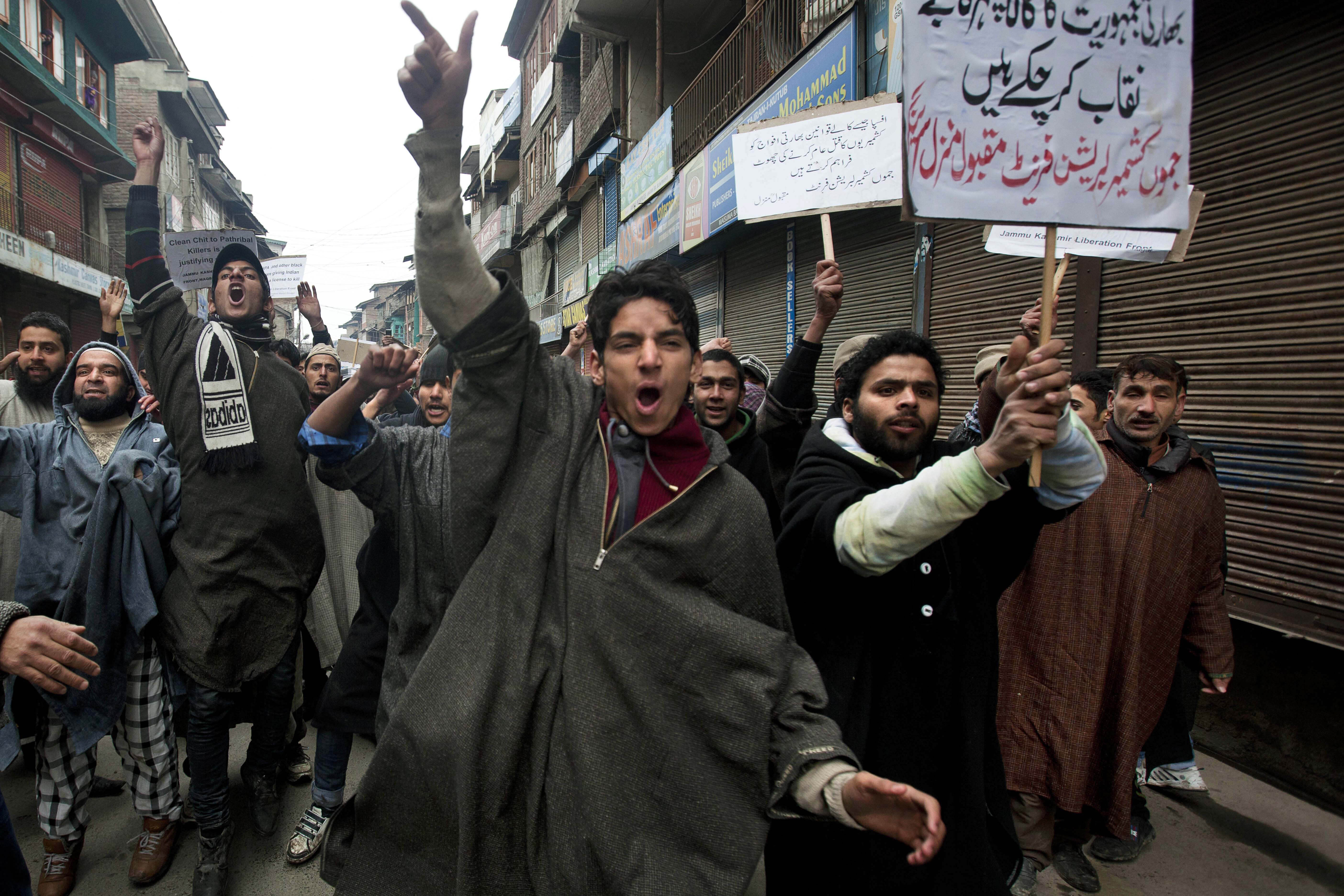"FILE - In this Friday, Jan. 31, 2014, file photo, Activists of Jammu Kashmir Liberation Front (JKLF) shout slogans during a protest against the Indian army's decision to close a fake encounter case against five soldiers in connection with the killing of five Kashmiris in Pathribal in March 2000, in Srinagar, India. In a separate case, the Indian military on Friday, Sept. 18, said its soldiers in Kashmir exceeded their legal powers in the killings of three local men it had described as Pakistani terrorists on July 18, 2020. Police ordered an investigation into the accusation of a staged gunbattle, and the results have not yet been released. The results of the police probe are likely to spark an outcry among Kashmiri activists who for years have accused Indian troops of abusing their powers and repeatedly targeting civilians. Placard at background right reads, ""AFSPA and other black laws are giving Indian soldiers a license to kill."" (AP Photo/Dar Yasin)"