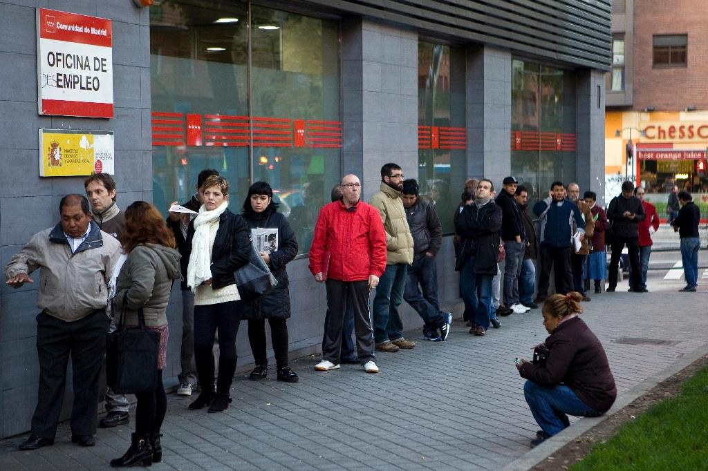 People wait in line at a government employment office in Madrid on December 2, 2014