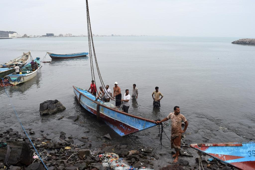 Yemeni men lift a damaged fishing boat out of the water after a tropical cyclone slammed into the southern port city of Aden, on November 3, 2015