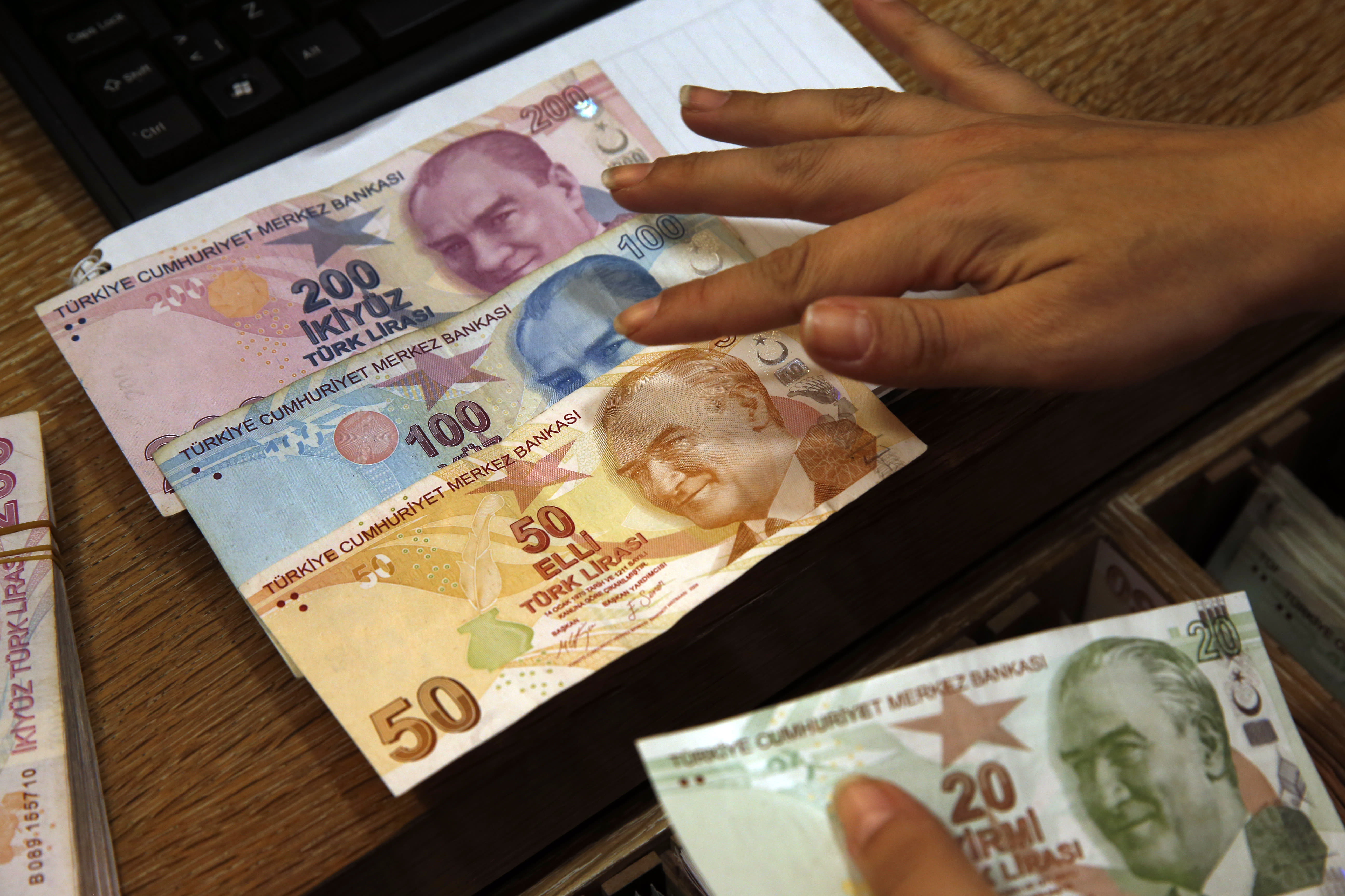 FILE- In this Wednesday, Aug. 15, 2018, file photo a worker at a currency exchange shop exhibits Turkish lira banknotes bearing pictures of modern Turkey's founder Mustafa Kemal Ataturk, in Istanbul. Investors have been pulling out of Turkey's markets, sending its stock market and currency plunging. That's making debt that Turkish companies owe in dollar terms even more expensive to pay back, which only further weakens the country's financial system. (AP Photo/Lefteris Pitarakis, File)