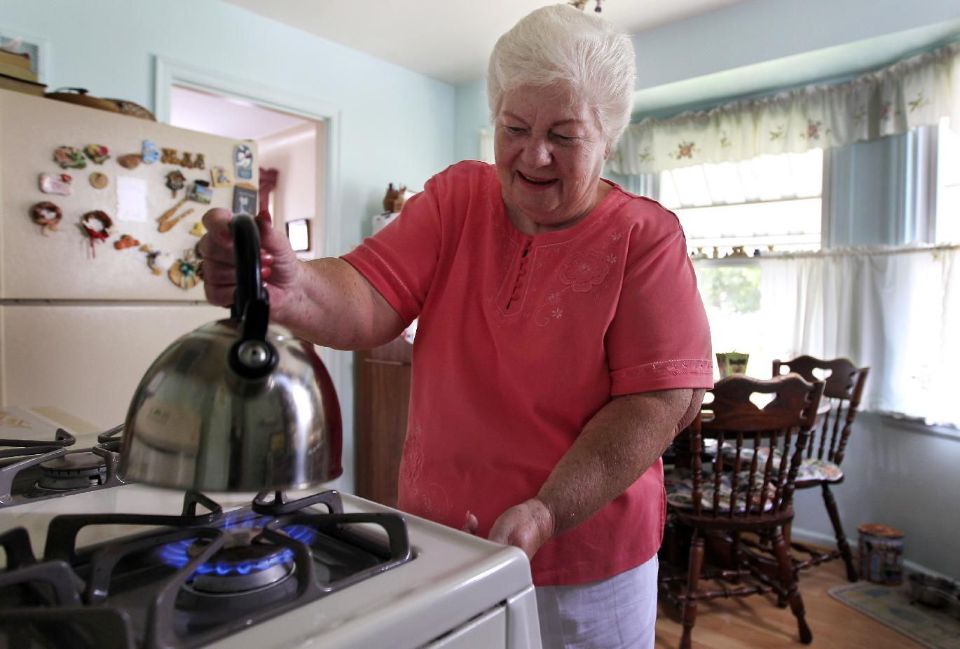 "In this photo taken July 26, 2012, Marge Youngs adjusts the flame on her stove at her home in Toledo, Ohio. When given a choice on how to fix Social Security's serious long-term financial problems, 53 percent of adults said they would rather raise taxes than cut benefits for future generations, according to an Associated Press-GfK poll. ""Right now, it seems like we're taxed so much, but if that would be the only way to go, I guess I'd have to be for it to preserve it,"" said Youngs, a 77-year-old widow. ""It's extremely important to me. It's most of my income."" (AP Photo/Carlos Osorio)"