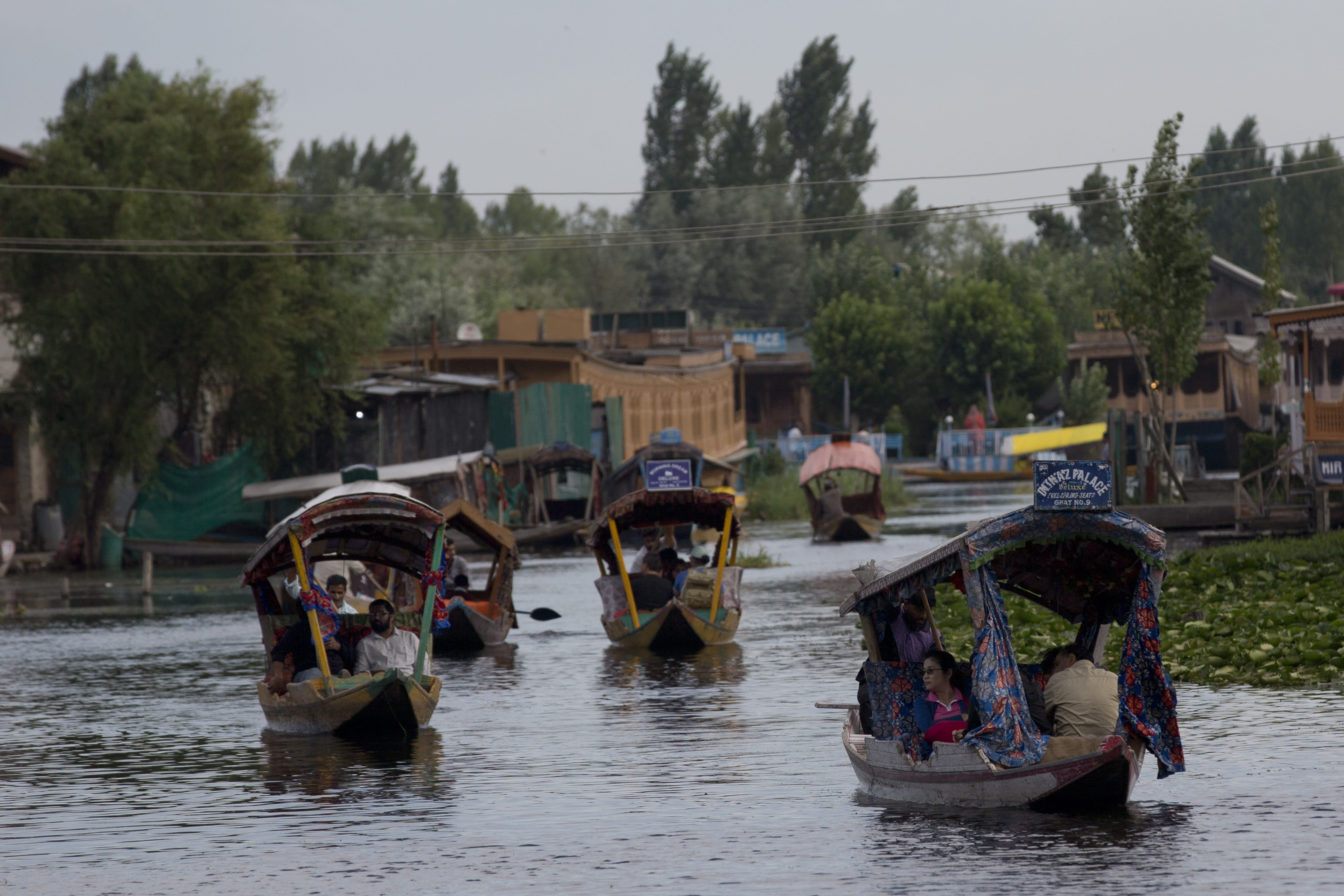 FILE - In this Saturday, Aug. 3, 2019, file photo, Tourists in Shikaras, a traditional gondola, cross the Dal Lake as they prepare to leave Srinagar, Indian controlled Kashmir. Authorities in Indian-controlled Kashmir are allowing tourists back into the region two months after ordering them to leave, citing security concerns. The local government had instructed tourists and Hindu pilgrims to leave on Aug. 2, three days before India stripped the Muslim-majority region of its statehood and special semi-autonomous status. (AP Photo/Dar Yasin, File)