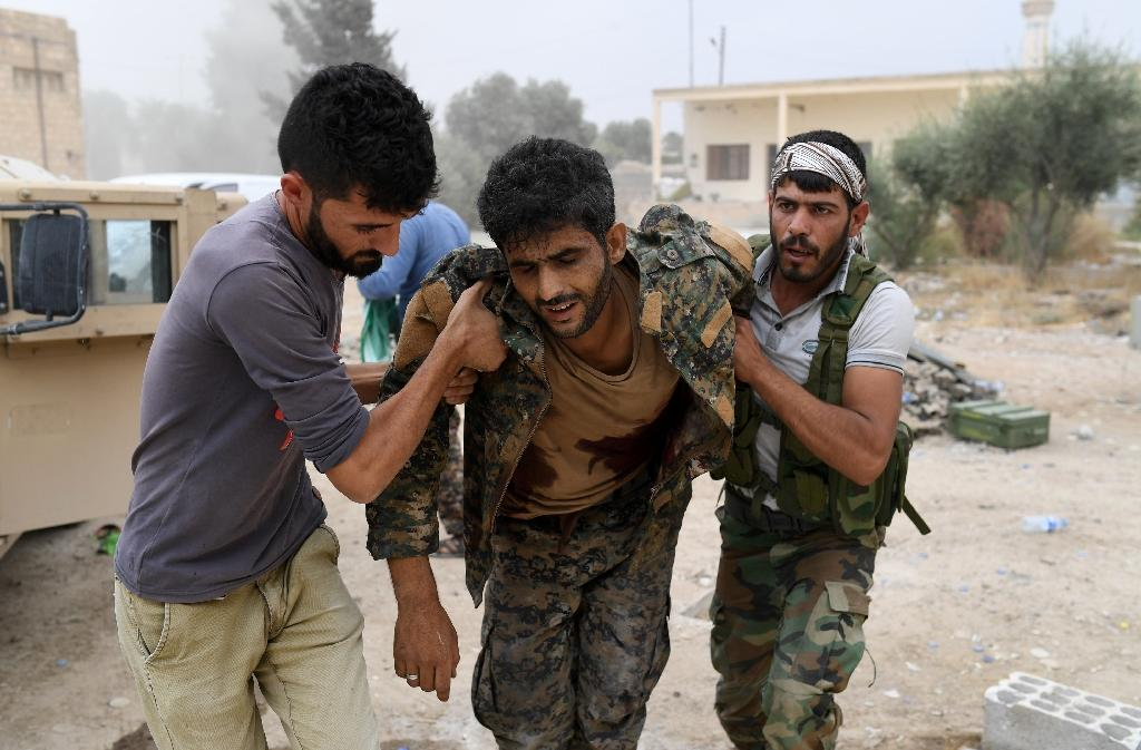 Members of the Syrian Democratic Forces carry wounded comrade Ibrahim (C) towards an armoured vehicle to drive him to a medical centre after he was shot by a jihadist sniper on the eastern frontline of Raqa (AFP Photo/BULENT KILIC)